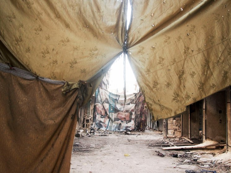 SYRIA. Aleppo. March 23, 2013. Makeshift sheets and blankets sewn together obstruct the view from regime snipers in the Al-Amiriya front line of city.
