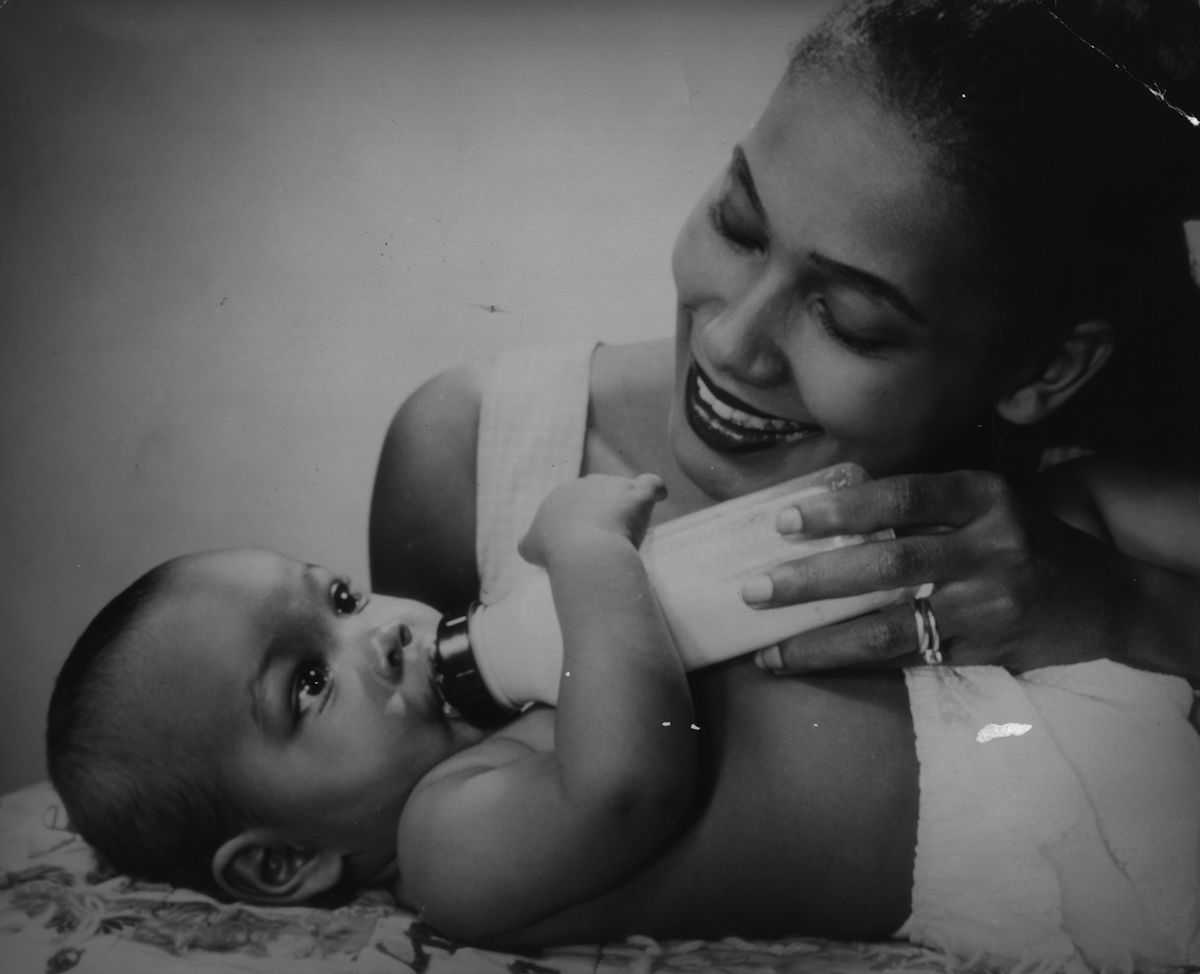 circa 1960:  A mother feeds her baby a bottle.