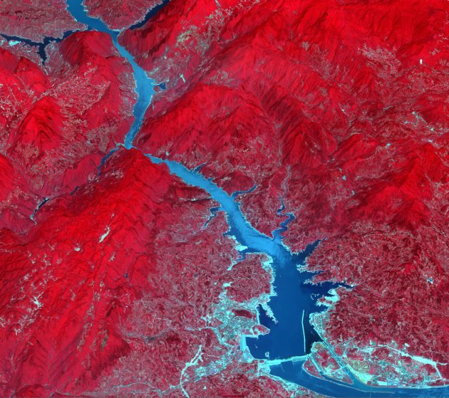 The Three Gorges Dam spans the Yangtze River in east-central China. Since its completion in 2008, over 1.3 million people were relocated; 13 cities, 140 towns, and 1350 villages were submerged; and the cost of the project exceeded $40 billion. Vegetation appears red at the near-infrared wavelengths captured here. The image was acquired June 24, 2009.