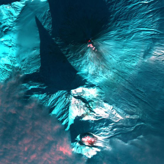 Red glows indicate the presence of heat from Bezymianny volcano (bottom) and Klyuchevskaya volcano (top) in Kamchatka, Russia acquired on Jan. 21, 2004.