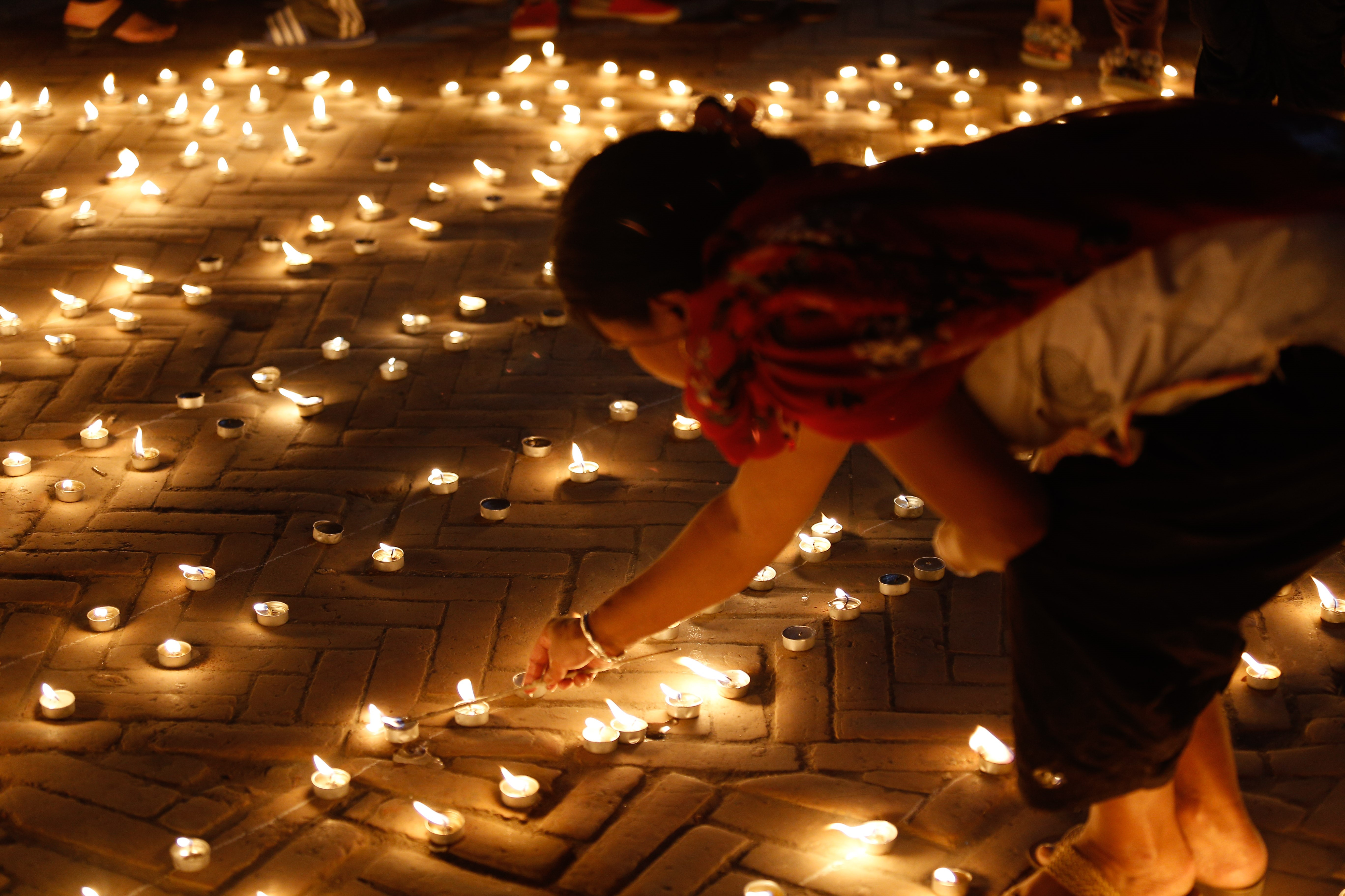 Nepalese woman lights a candle to pay homage to earthquake victims as they mark the 1st anniversary in Kathmandu, Nepal on April 24, 2016.
