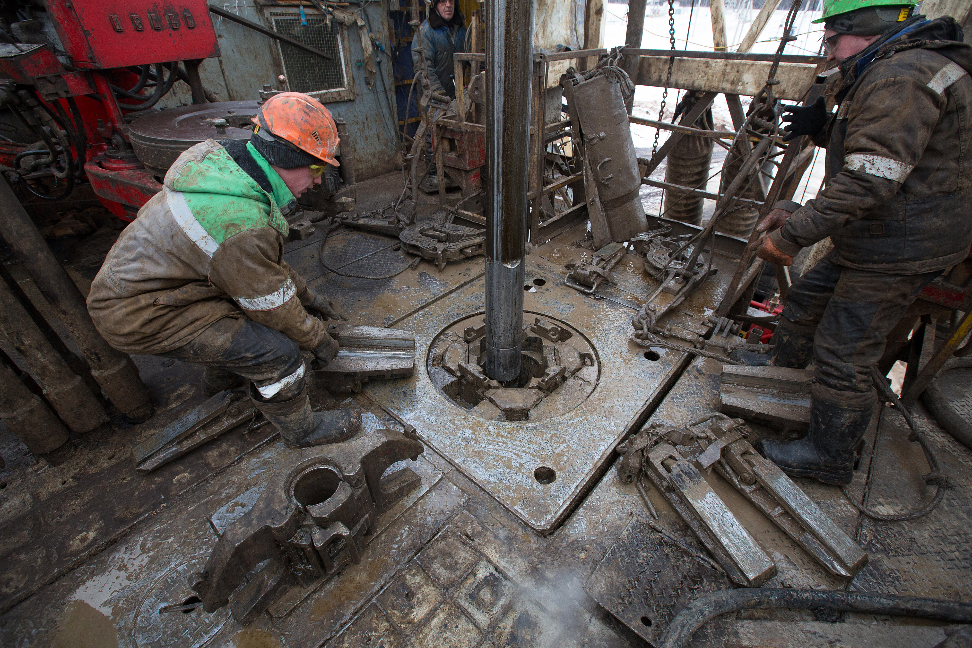 Oil workers adjust a pipe section at the turntable on an oil derrick during drilling operations by Targin JSC, a unit of Sistema JSFC, in an oilfield operated by Bashneft PAO in the village of Otrada, 150kms from Ufa, Russia, on Saturday, March 5, 2016.