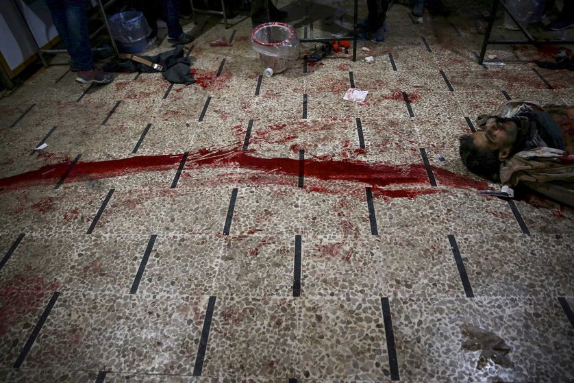 The body of a dead man is seen next to blood stains at a field hospital, after what activists said were air and missile strikes, in the Douma neighborhood of Damascus, Syria, Dec. 13, 2015.