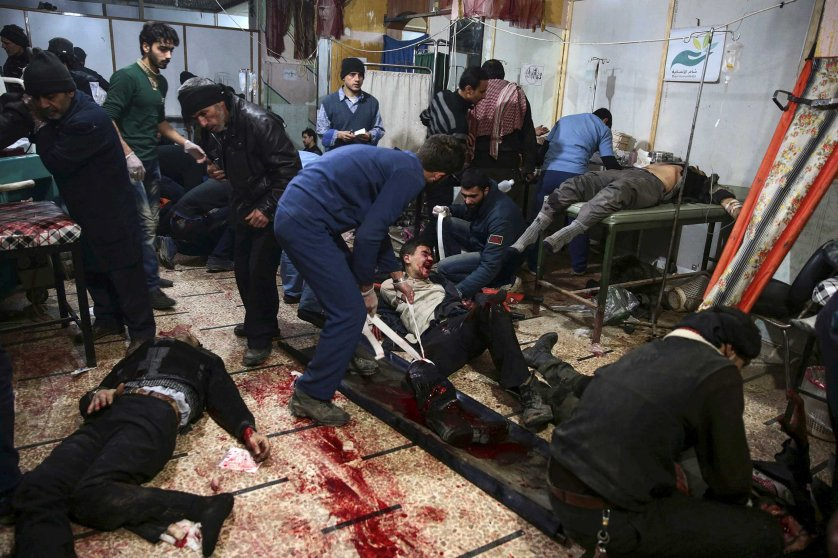 Medics treat injured people inside a field hospital after what activists said were air and missile strikes in the Douma neighborhood of Damascus, Syria December 13, 2015.