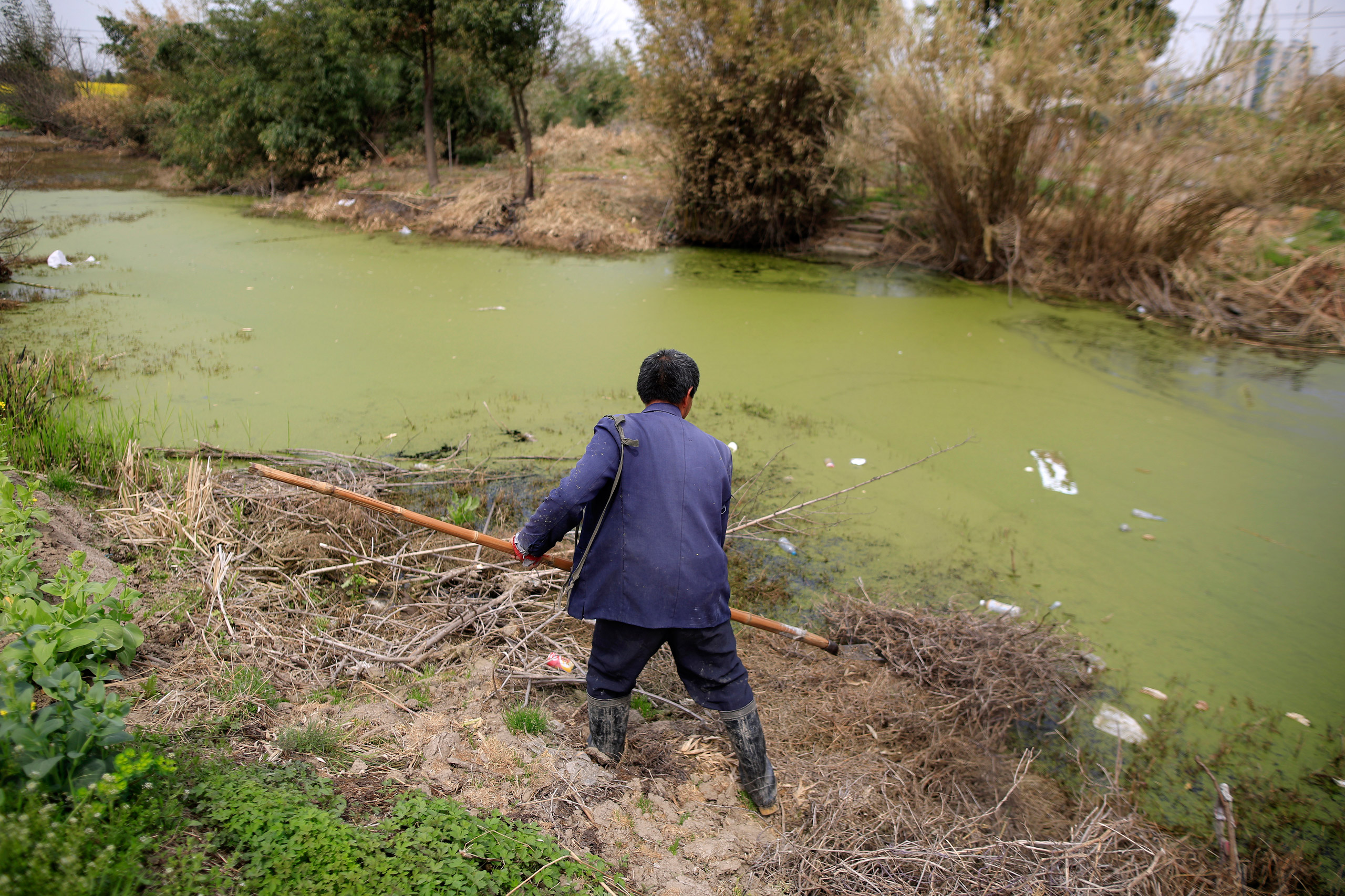 A farmer works on a polluted river in Shanghai, China, on Mar. 21, 2016.