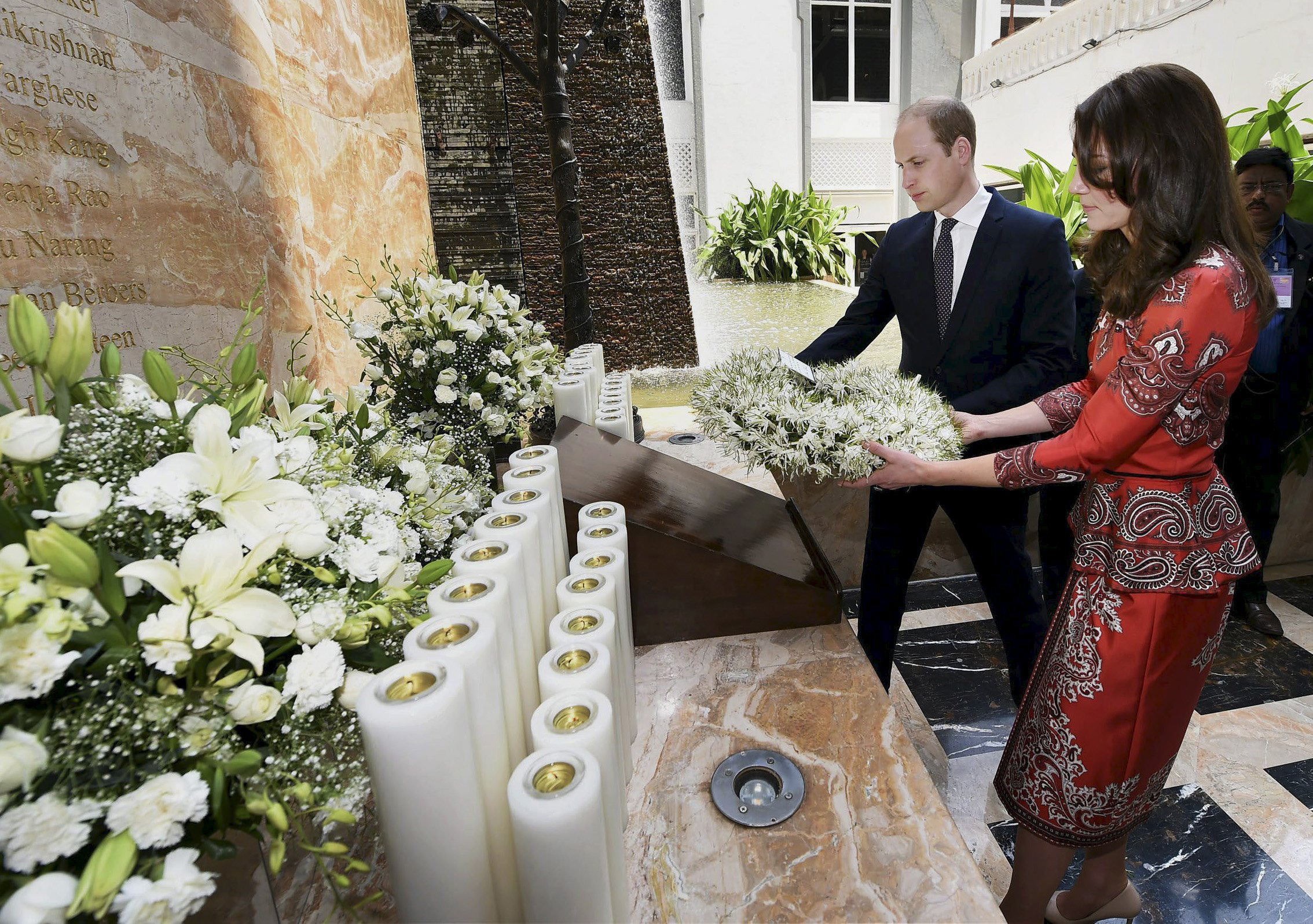 Prince William and Catherine hold a wreath as they pay their respects at the 26/11 memorial at the Taj Mahal Palace hotel, one of the sites of the 2008 attacks, in Mumbai, India, on April 10, 2016.