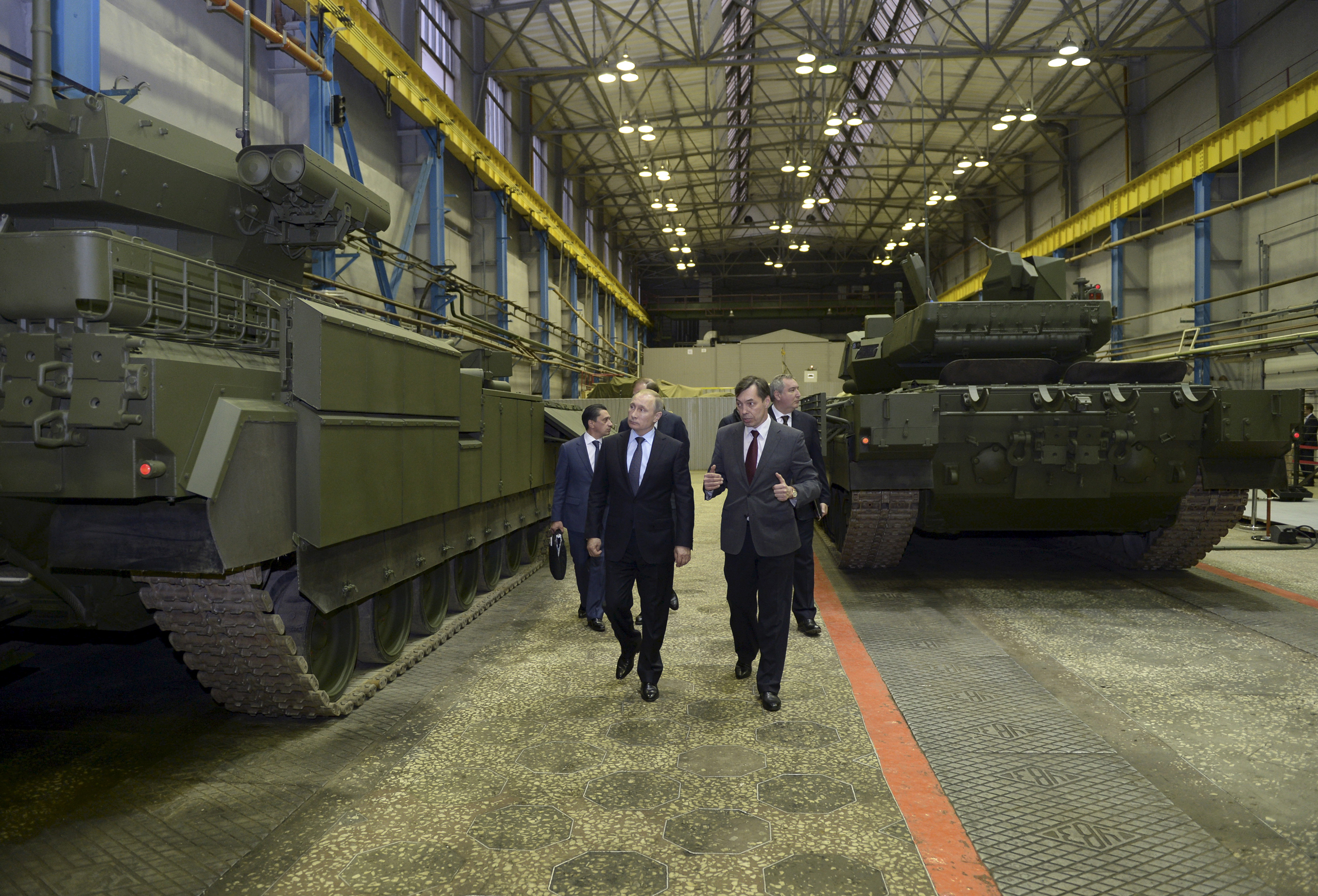 Russian President Vladimir Putin and Andrei Terlikov, the head of the Ural Transport Machine Building Design Bureau, walk by a Russian infantry fighting vehicle and a battle tank at the Uralvagonzavod factory in Nizhny Tagil, Russia, on Nov. 25, 2015.
