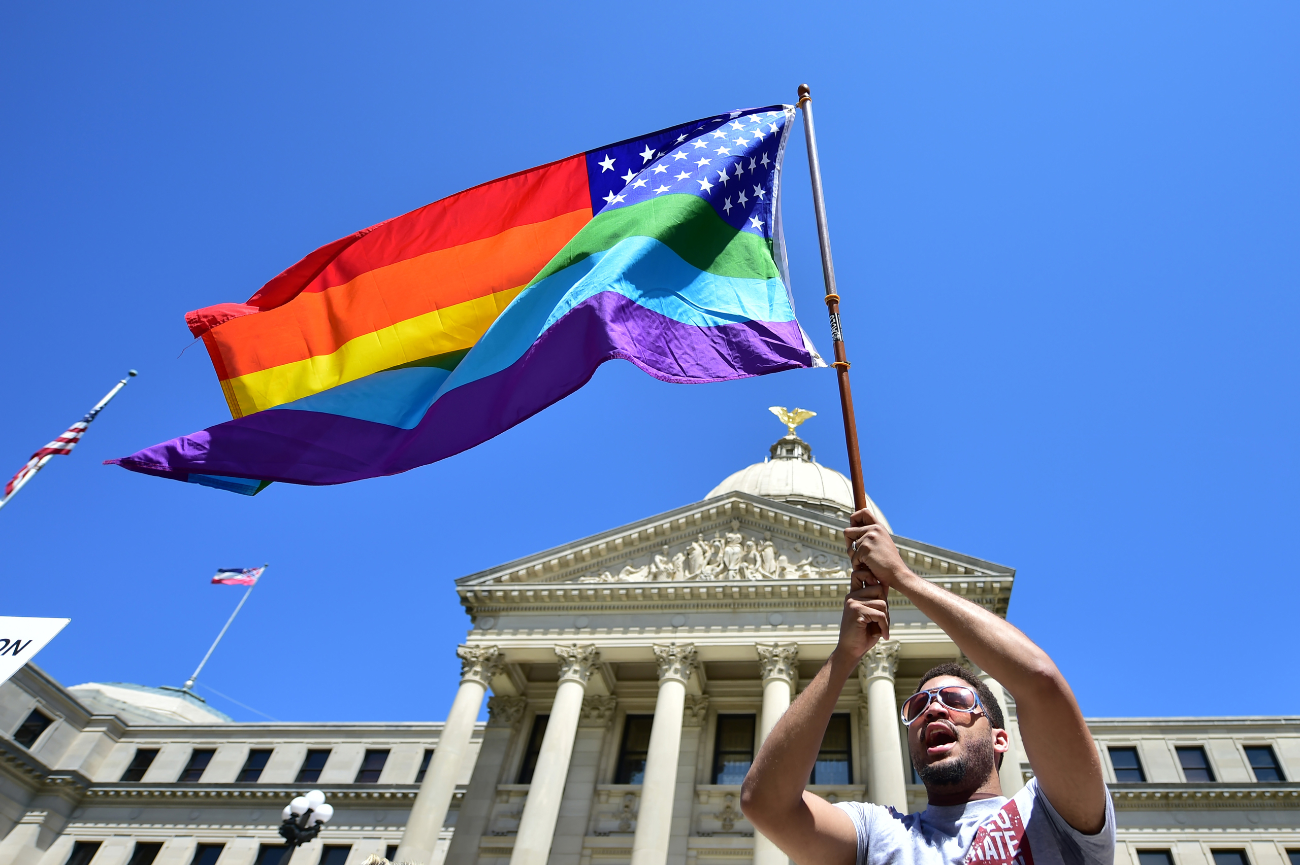 Meridian resident Nykolas Alford waves a rainbow-colored flag designed with the U.S. flag during a Human Rights Campaign protest of House Bill 1523 on the Mississippi State Capitol steps in Jackson, Miss., on Mar. 29, 2016.
