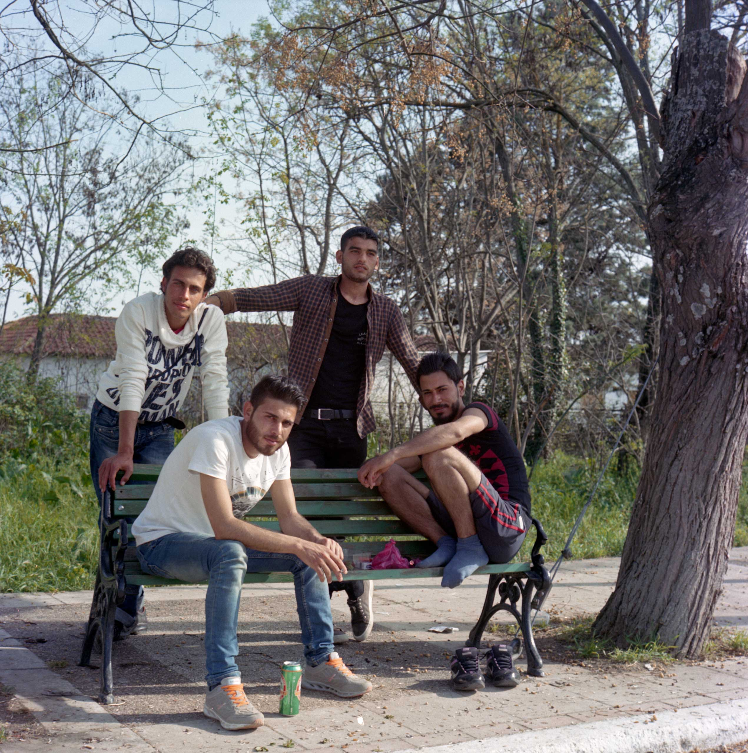 Young Syrian men rest in a park in Idomeni, Greece. April 2016.