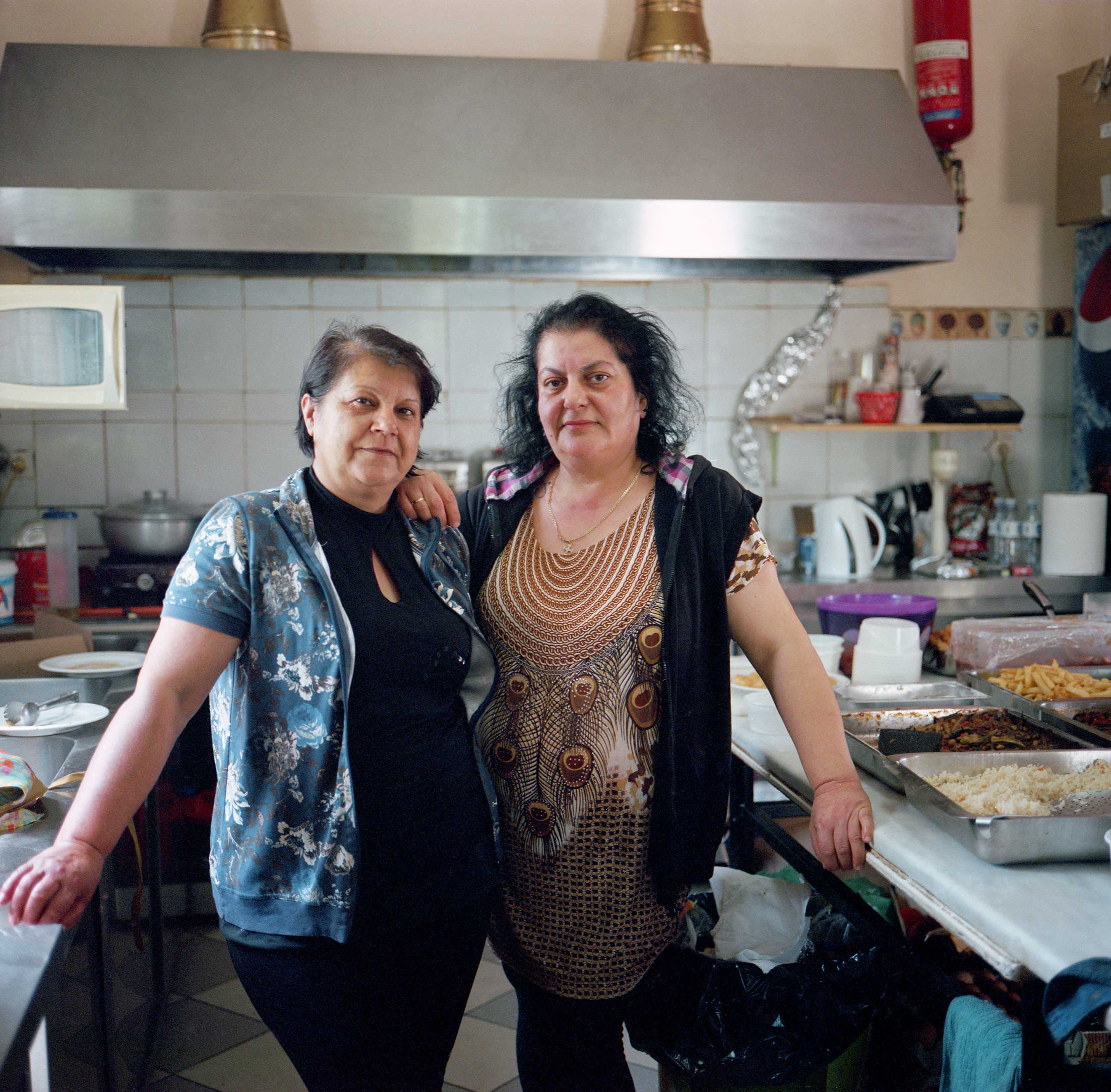 <b>Nopi Pantelidou (left) and Gianna Konstantinidou, villagers</b> Both women work in the kitchen at a cafe in Idomeni. A small canteen that used to serve local residents and others passing through the Idomeni train station is now overflown with refugees. Idomeni, Greece, April 2016.