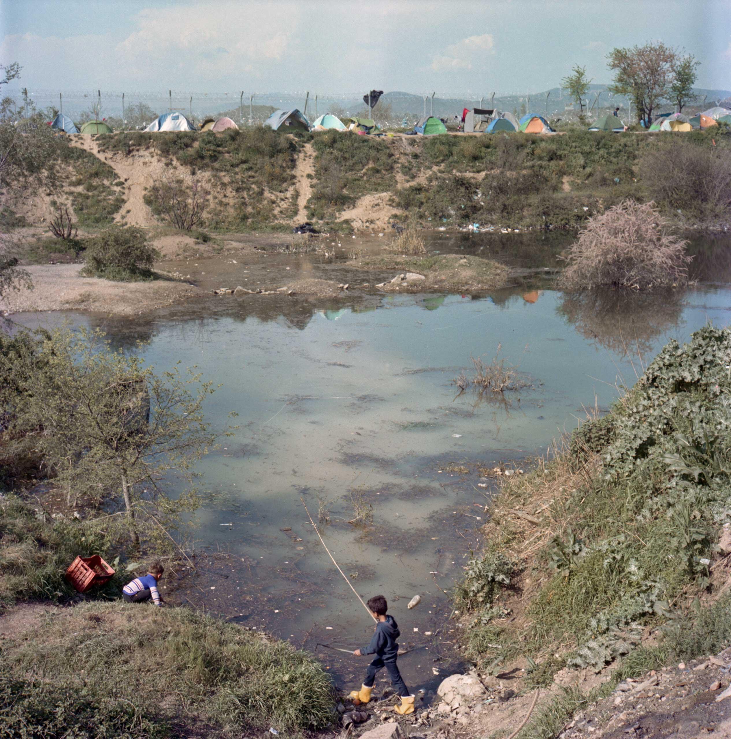 Boys play by the pond near the border with Macedonia. Idomeni, Greece. April 2016.