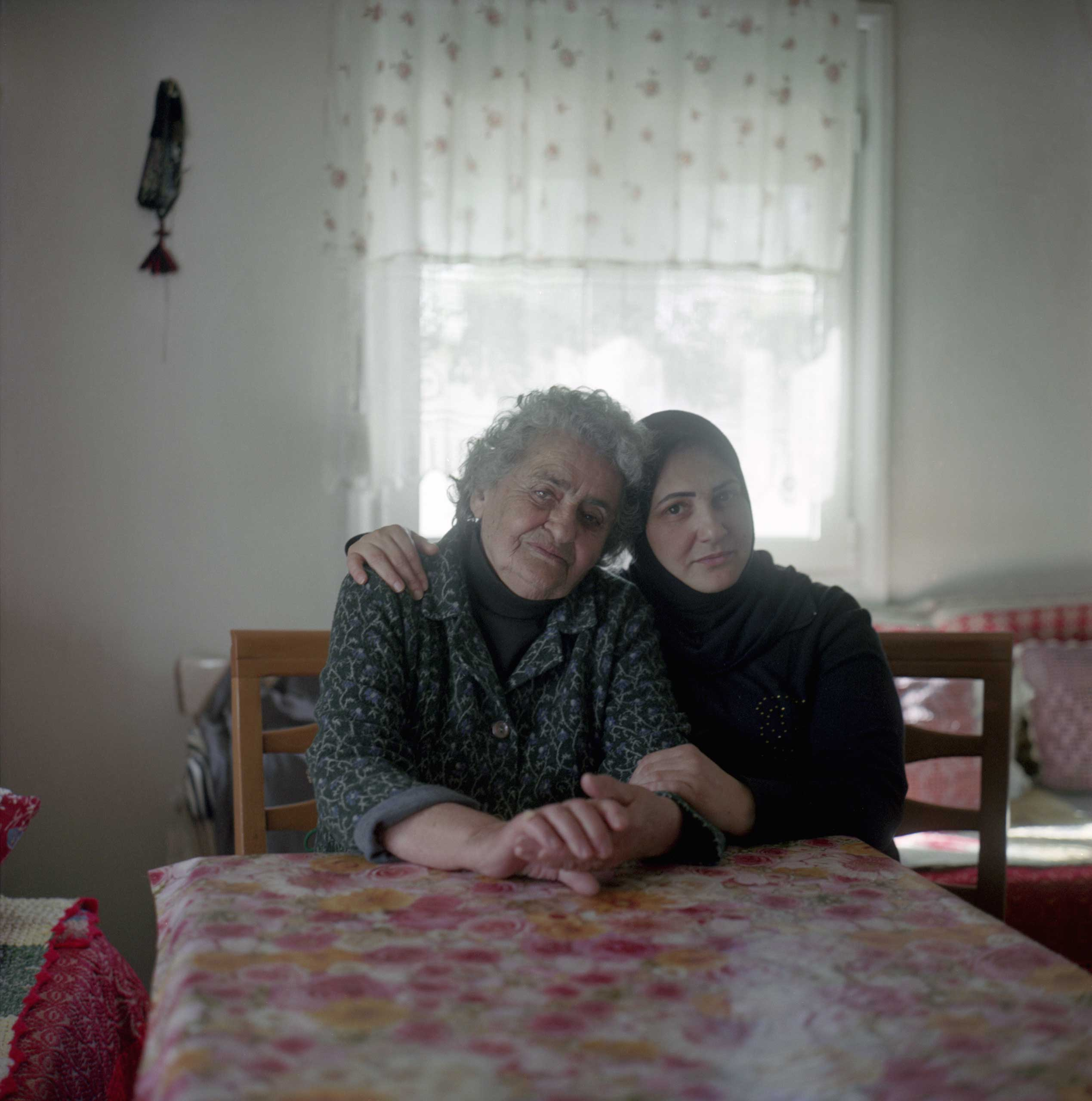 <b>Panagiota Vasiliadou, 82, villager, and Saha, a 30-year-old refugee from Syria</b> Panagiota Vasiliadou hosts eight Syrian refugees in her home.  Panagiota is paying for food, while the women help cook the meals. Her water and electricity bill more than doubled since she has welcomed them in her home. She says she cannot afford to support eight adults with her pension of 400 Euros a month, but she does not know how to tell them to leave. Idomeni, Greece. April 2016.