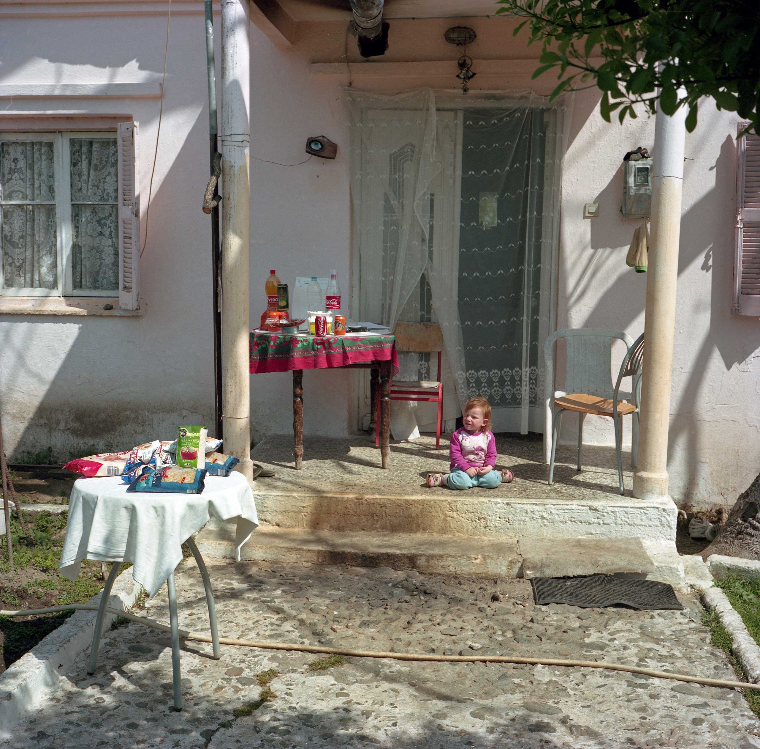 Packaged food and snacks for sale in the courtyard of an Albanian family that had come to Idomeni, Greece as refugees 25 years ago. The family members sell food and drinks to the refugees from the porch of their home. Idomeni, Greece. April 2016.