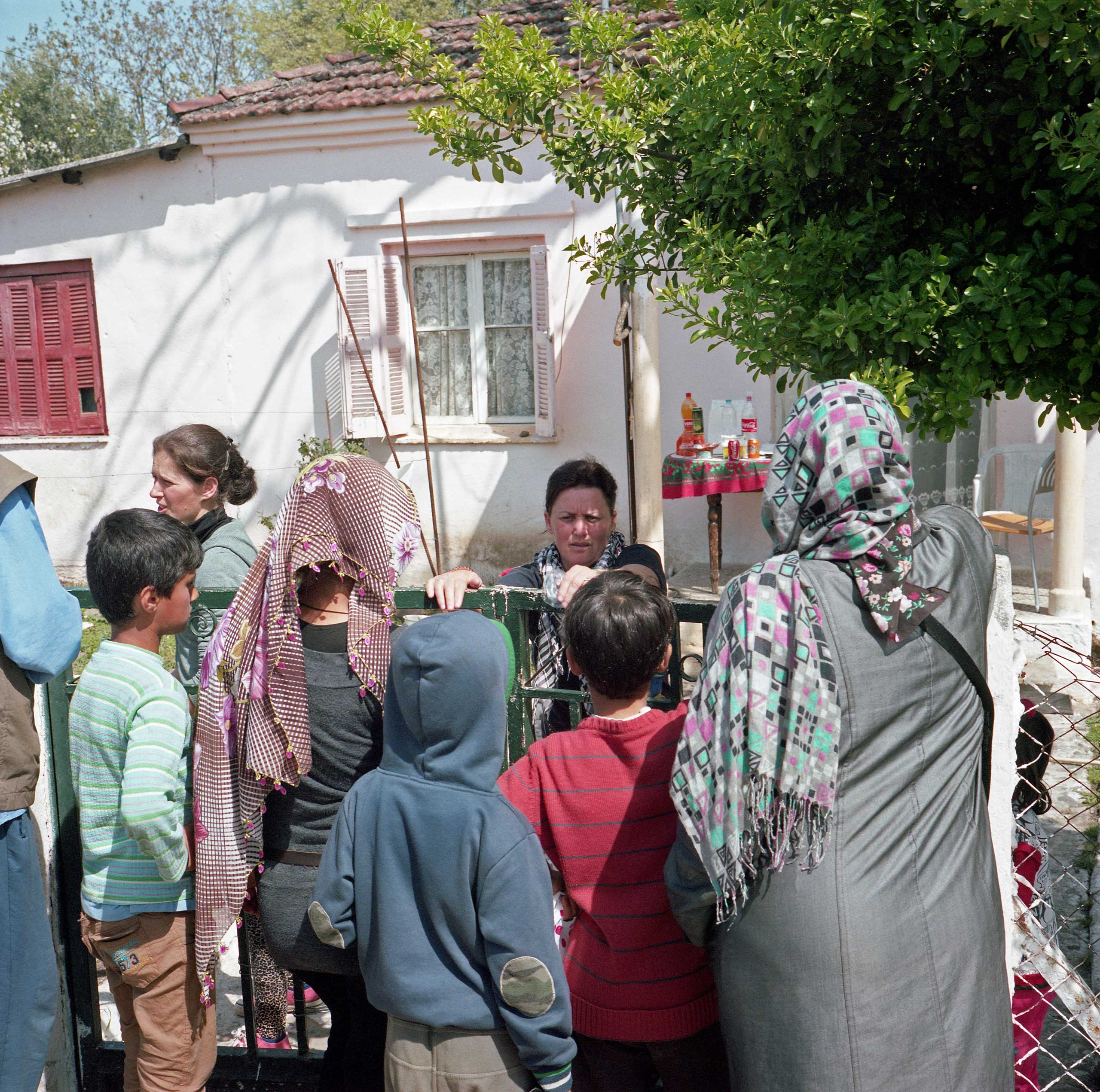Members of an Albanian family, themselves refugees, sell food and drinks to the newly arrived refugees from the porch of their home in Idomeni, Greece. April 2016.