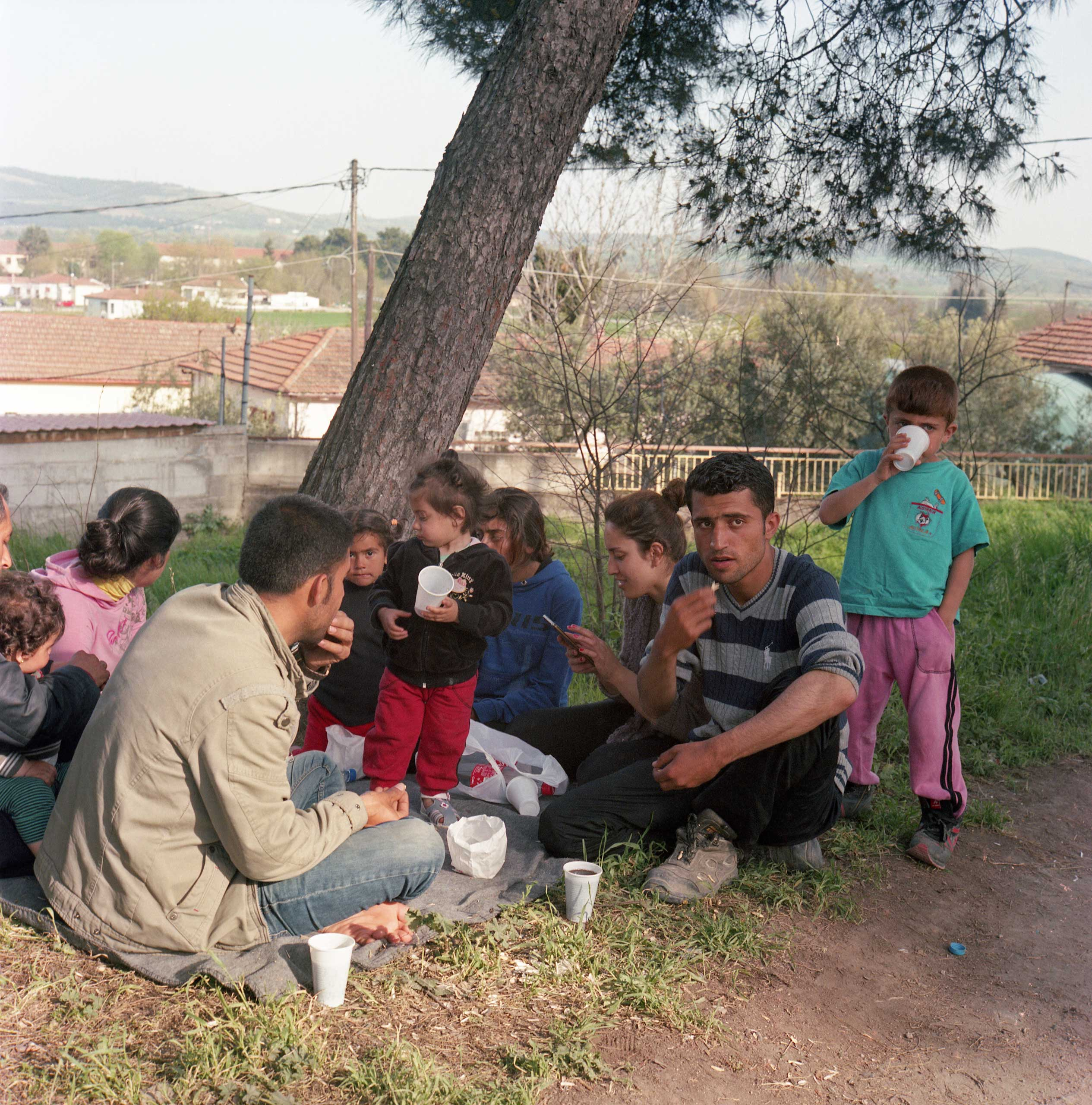 A Syrian family eats in a park in Idomeni, Greece. April 2016.