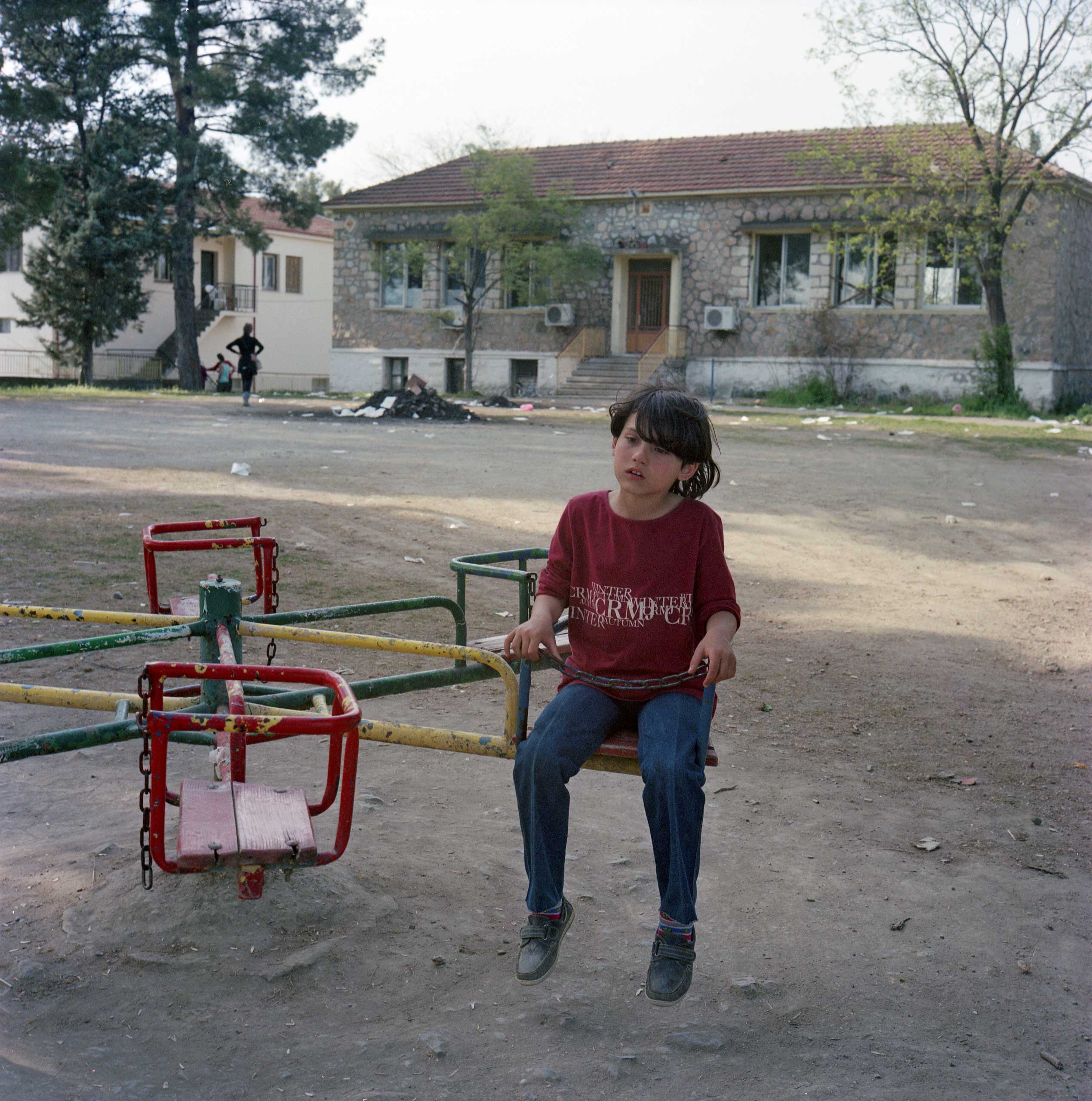 A Syrian girl plays in a park outside a school in Idomeni. The school was used as storage for food supplies until it was recently looted. Idomeni, Greece. April 2016.