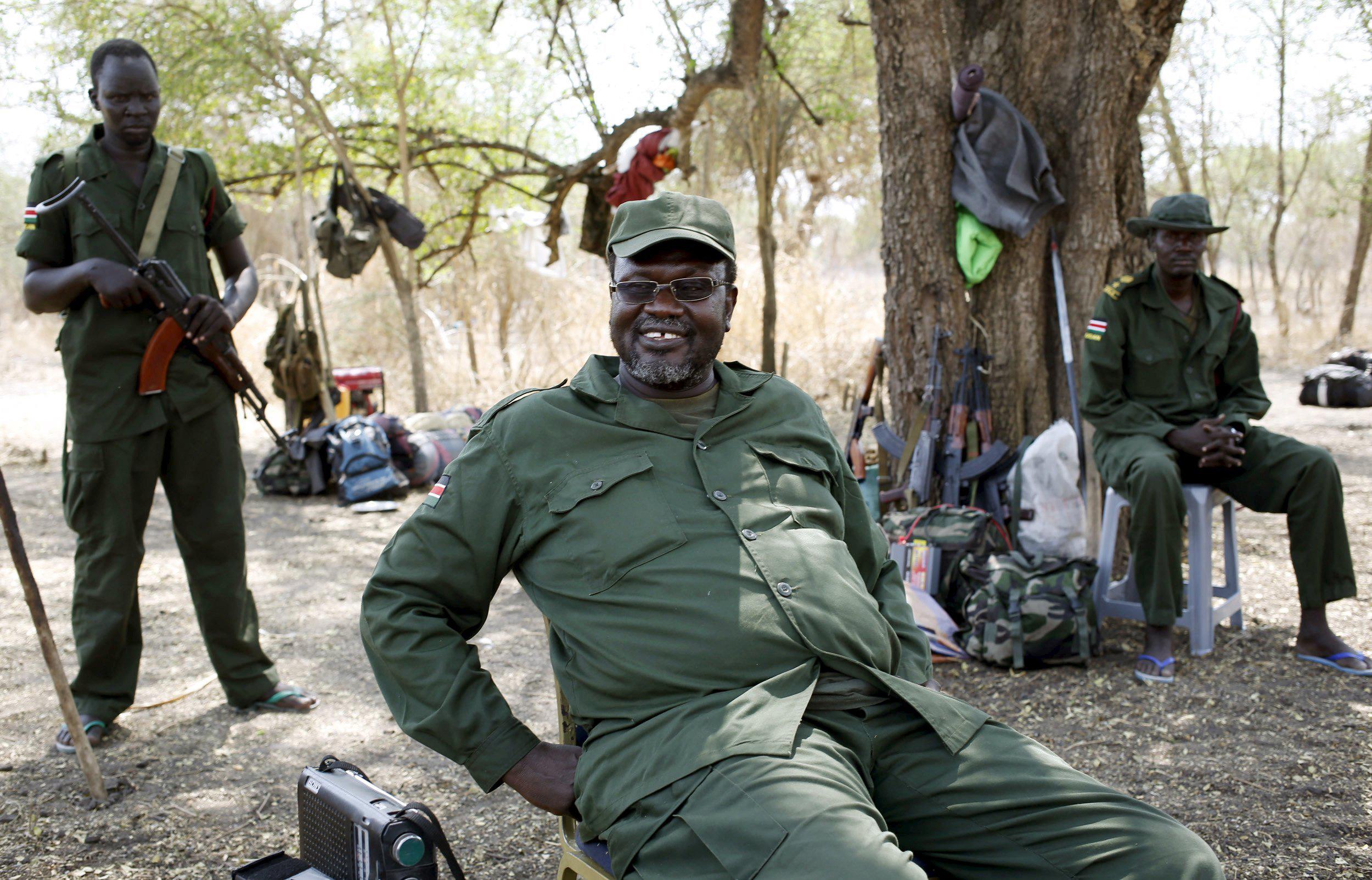 South Sudan's rebel leader Riek Machar sits near his men in a rebel-controlled territory in Jonglei State, South Sudan Jan. 31, 2014.