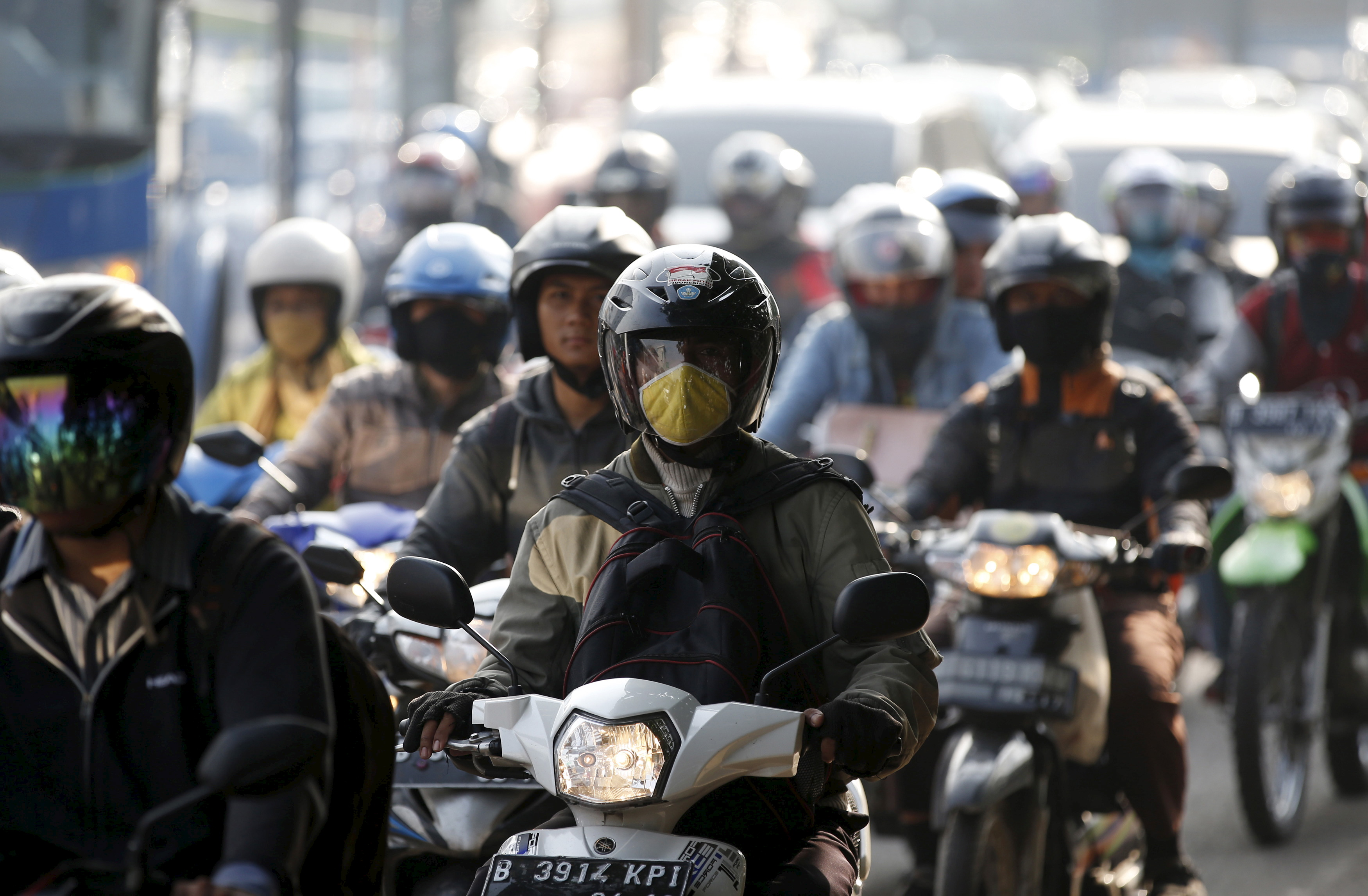 Motorcyclists ride on a major route next to a toll road into Jakarta on Feb. 25, 2015
