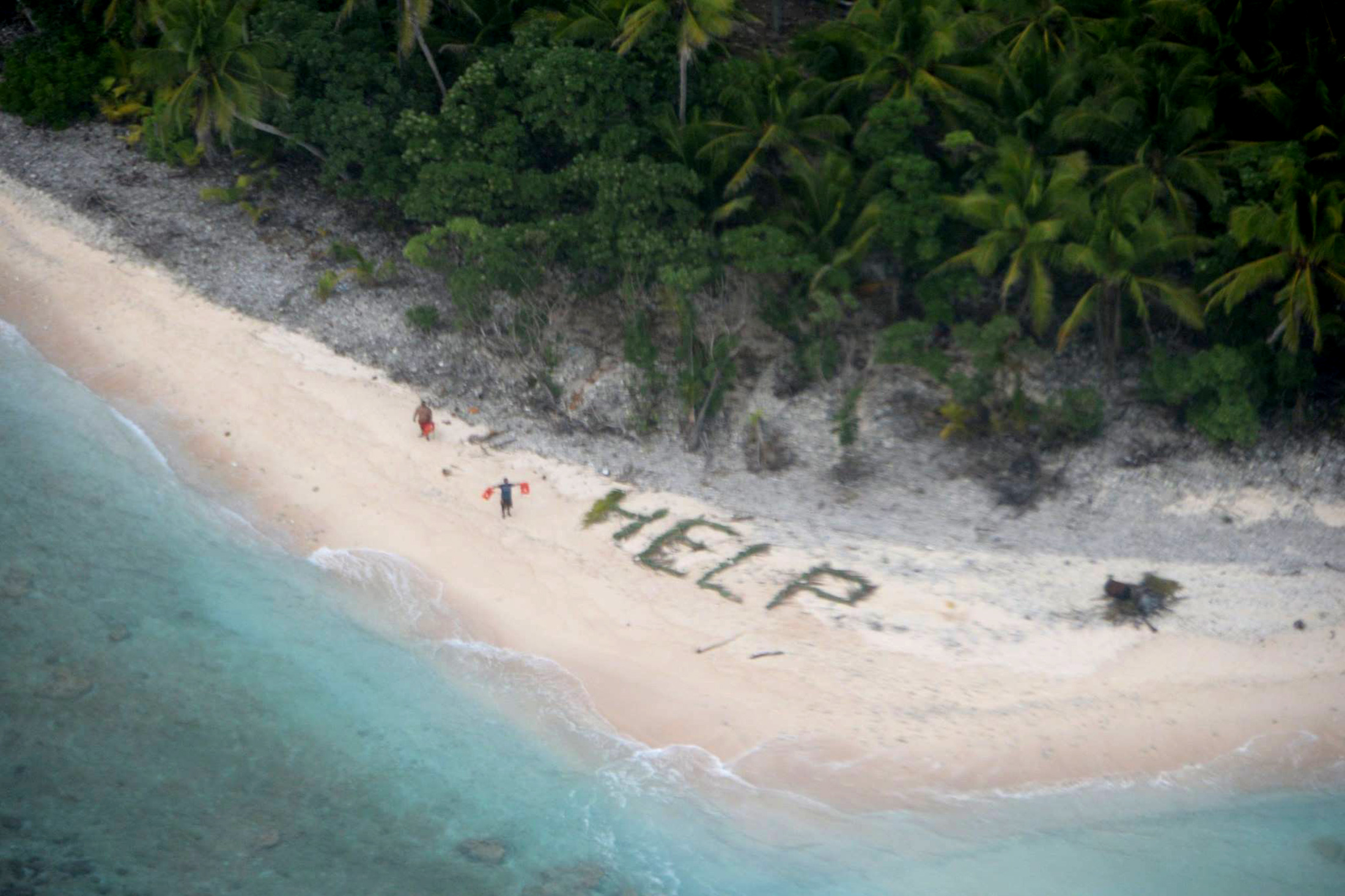 Two of three men stranded on the uninhabited island of Fanadik in Micronesia wave life jackets next to palm fronds spelling the word  HELP.