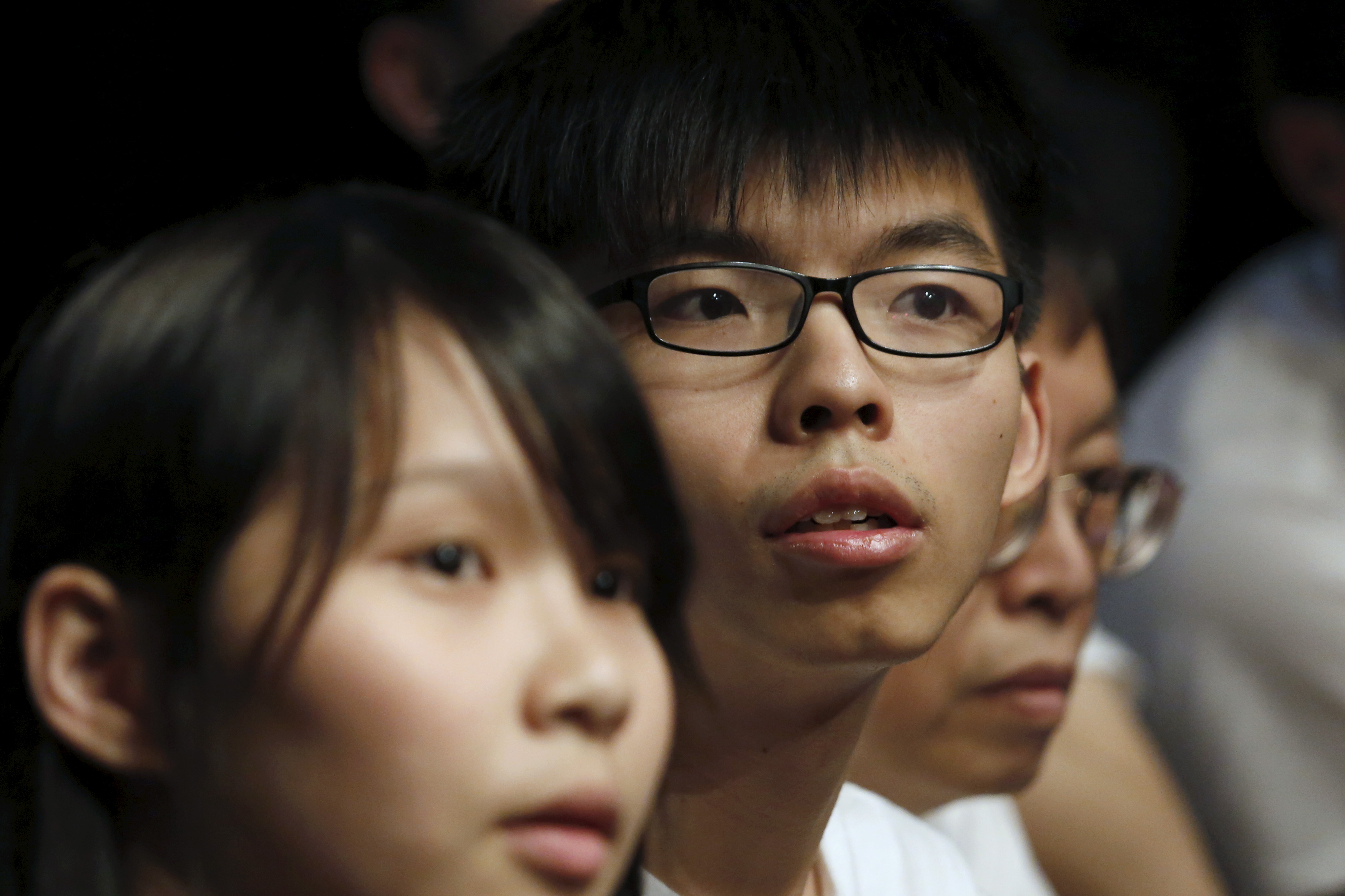 Student leaders of Occupy Central movement Joshua Wong, center, and Agnes Chow, left, attend the launching ceremony of their new political party Demosistō in Hong Kong on April 10, 2016