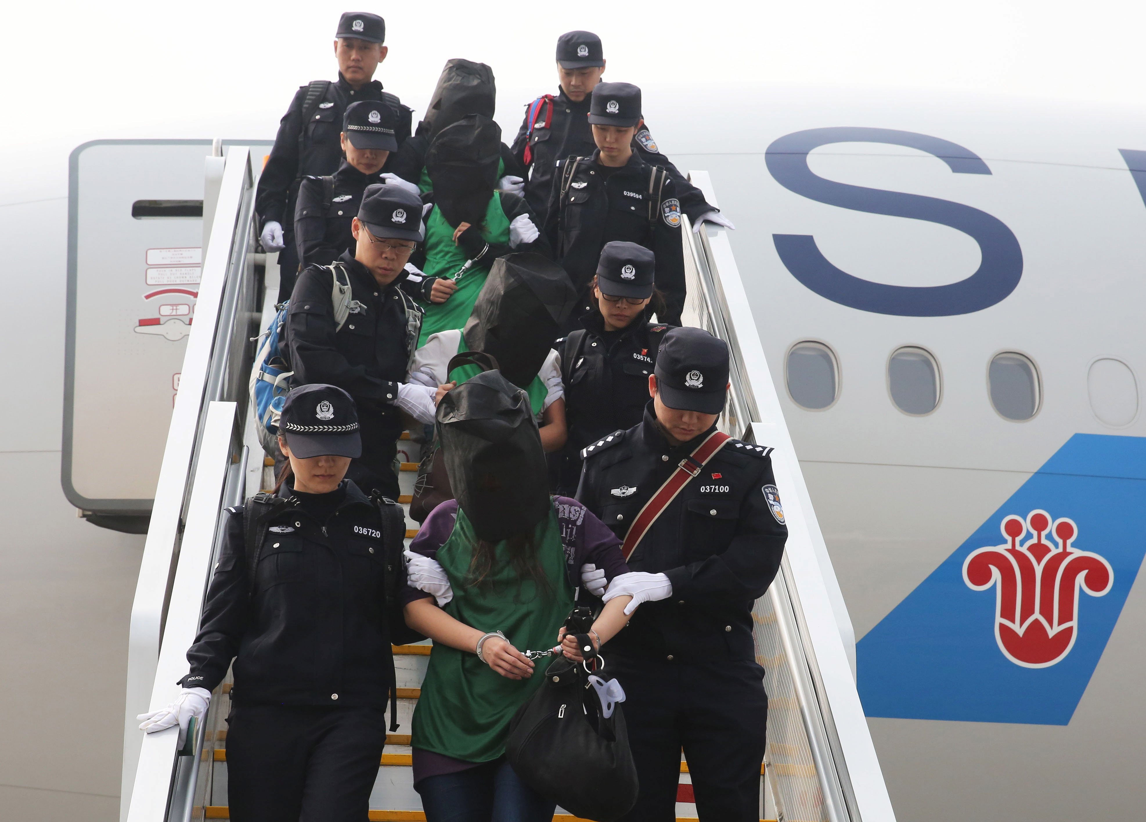 Police escort a group of people wanted for suspected fraud in China, after they were deported from Kenya, as they get off a plane at Beijing Capital International Airport in Beijing on April 13, 2016