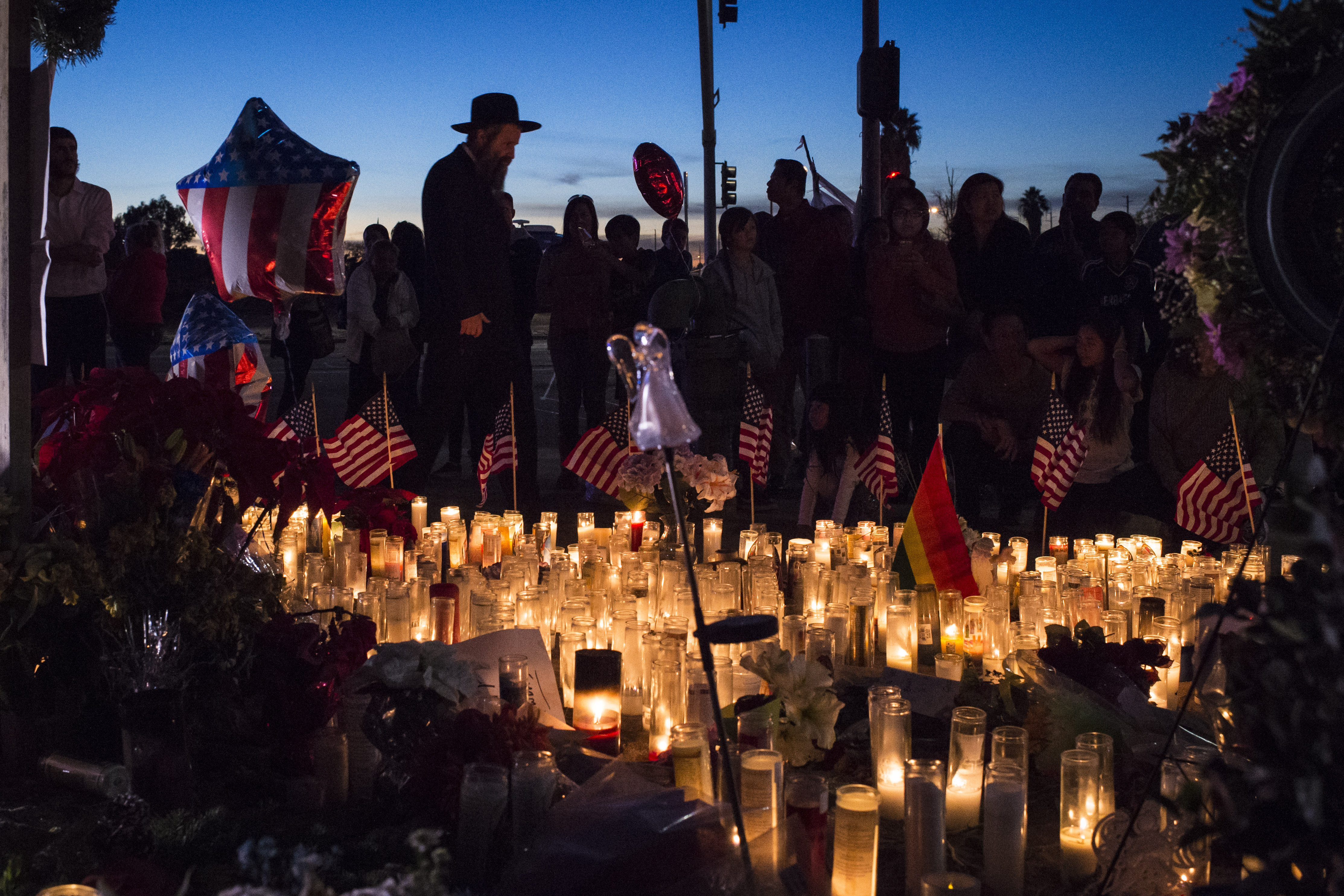 People pay their respects near the location of the mass shooting in San Bernardino, CA, on Dec. 6, 2015.