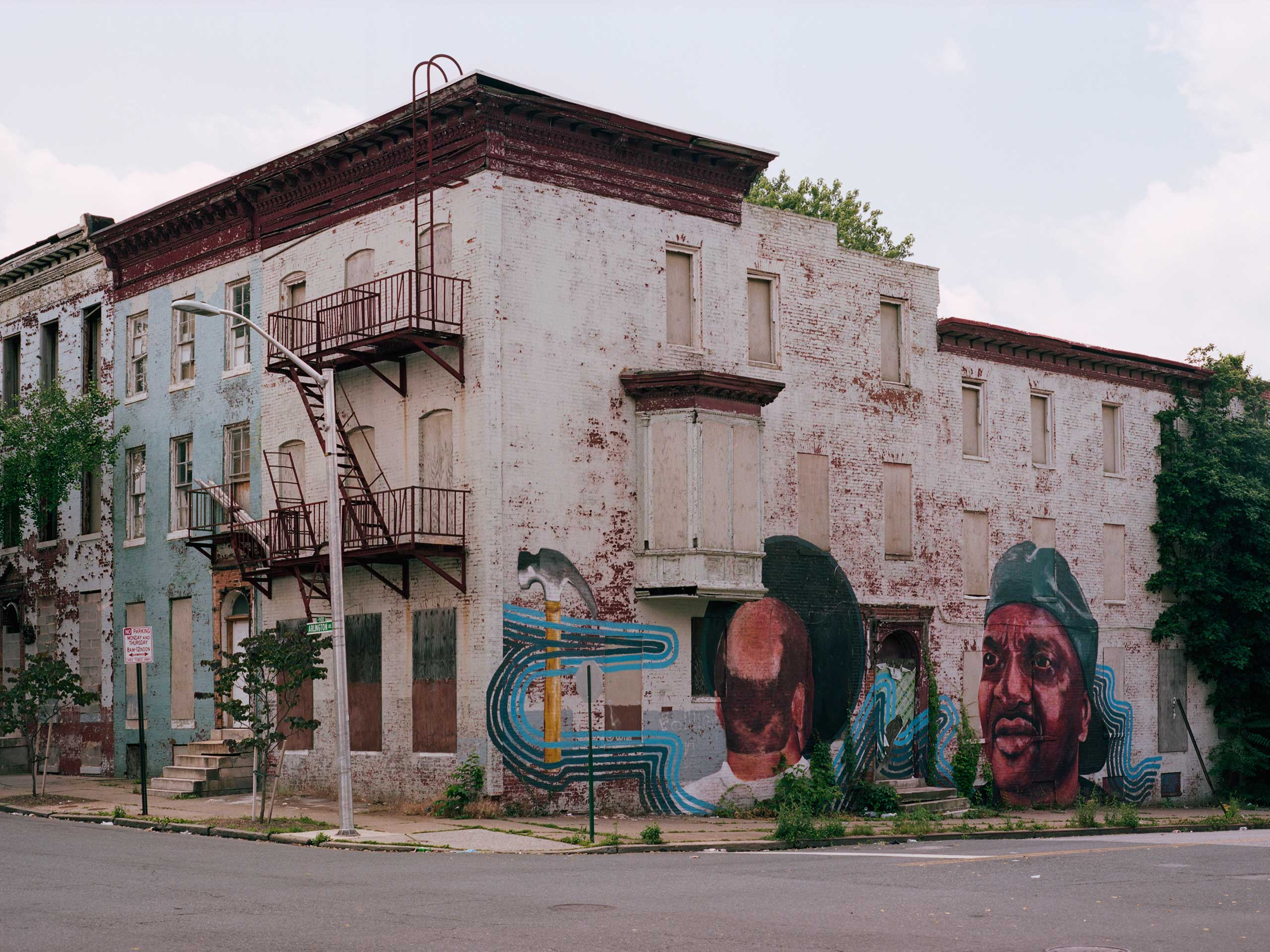 A mural adorns a set of vacant row houses on the corner of Arlington Avenue and Mosher Street in Sandtown. The mural is said to depict a local man who used to fix bikes in the neighborhood. Just a block away at Mosher and North Fremont Avenue is where the Baltimore Police van holding Freddie Gray stopped at an unknown time on April 12, 2015.