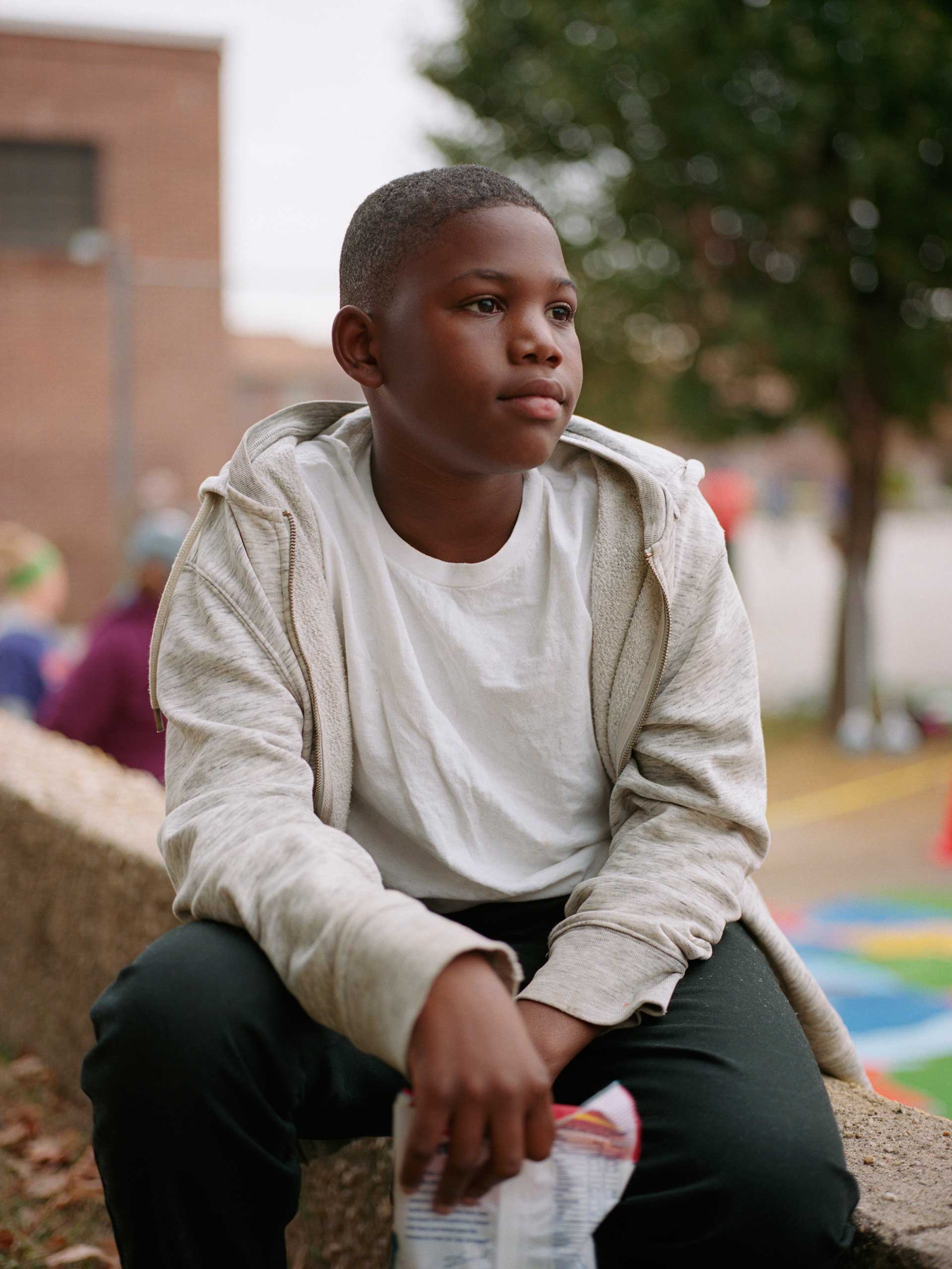 """Donnell Rochester, 12, hanging out in the playground at Gilmor Elementary School in Sandtown where he attended school. He currently lives in the Gilmor Homes housing project with his family, but they plan to leave Sandtown. """"I'm happy I'm getting out of here. We're basically moving to Hartford County. Everything is working out as planned. Gilmor Projects is something else. Gilmor Projects, they do anything in Gilmor Projects, it's a lot of shootings, it's a lot of killings. It's just everything. Basically a child wouldn't want to grow up in Gilmor. I know I didn't."""""""