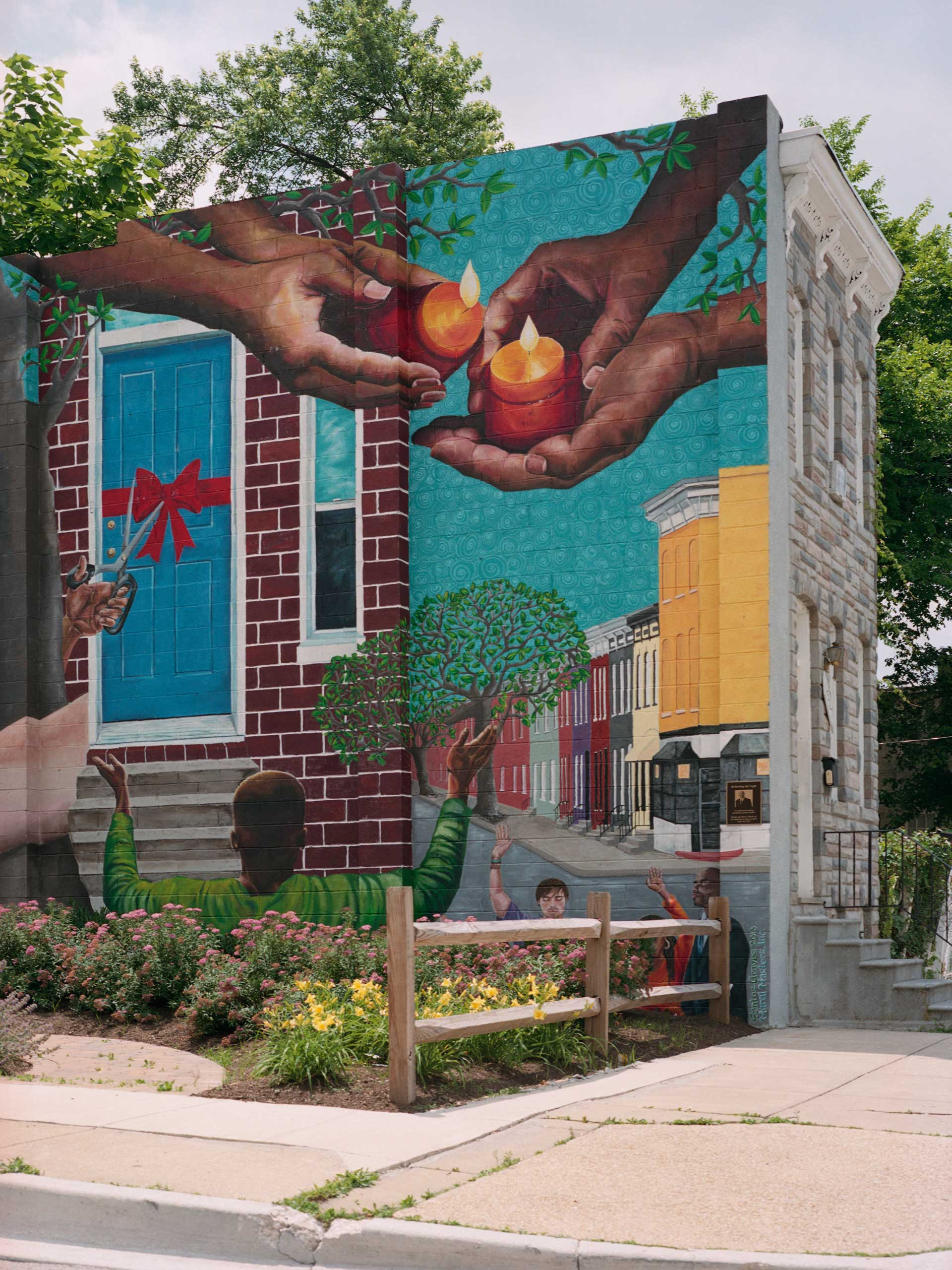 A mural adorns the exposed side of a row house near the corner of Baker Street and Leslie Street in Sandtown. The mural was painted in 2013 after the building on the corner burned down. It depicts both a community vigil and the construction of new homes by Habitat for Humanity. Over the span of 20 years Habitat for Humanity has renovated over 300 homes in the Sandtown neighborhood.