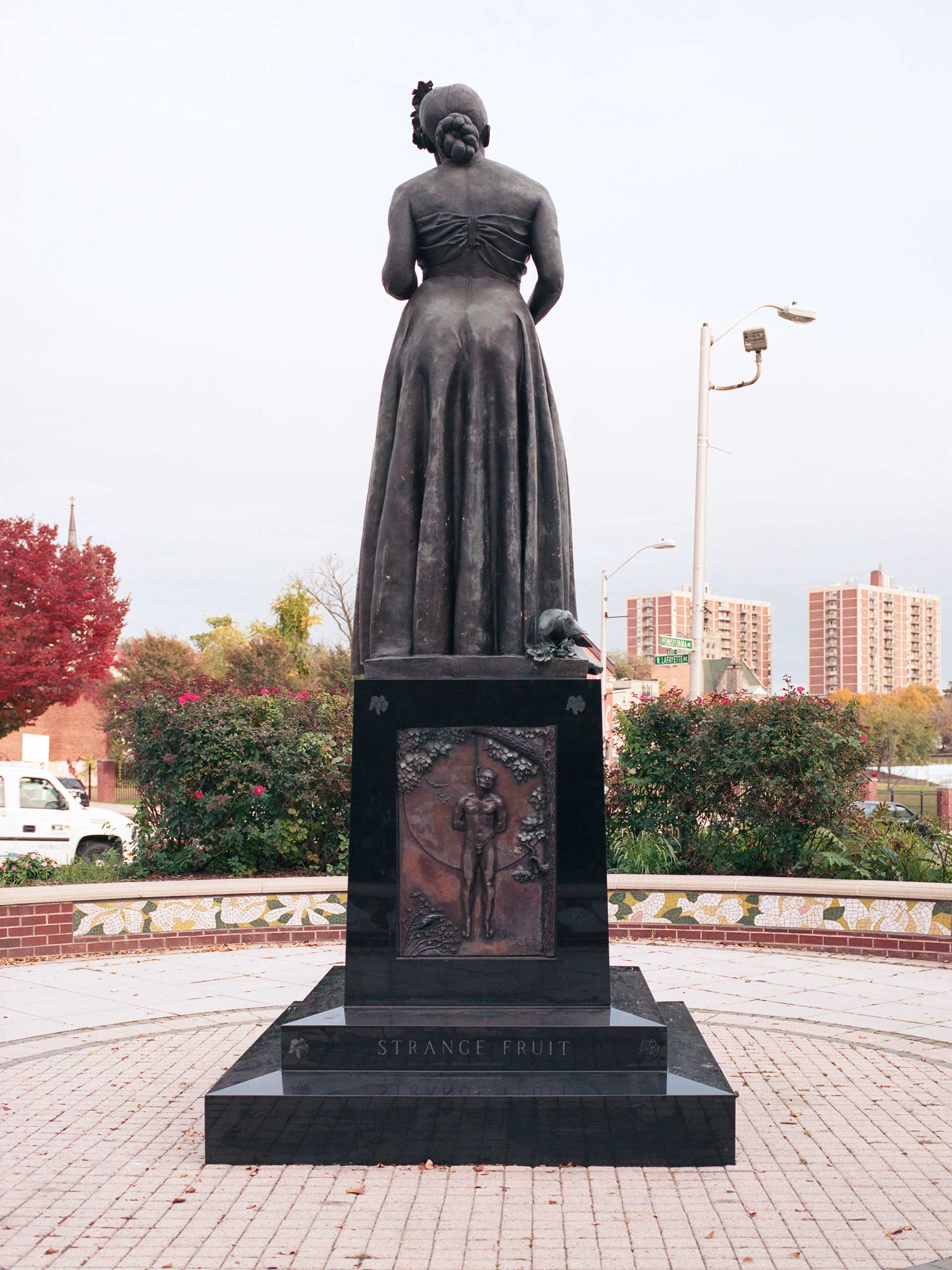 """A statue commemorating and depicting famed Baltimore musician Billie Holiday sits diagonally across the street from the original location of the Royal Theatre. The statue was first erected in 1985 but without its intended base, which was censored by the city at the time. The statue was rededicated in 2009 with its original base. The base features a lynching depiction, a reference to Holiday's song """"Strange Fruit"""", and a crow ripping apart a gardenia, Holiday's signature flower, to symbolize the Jim Crow era."""