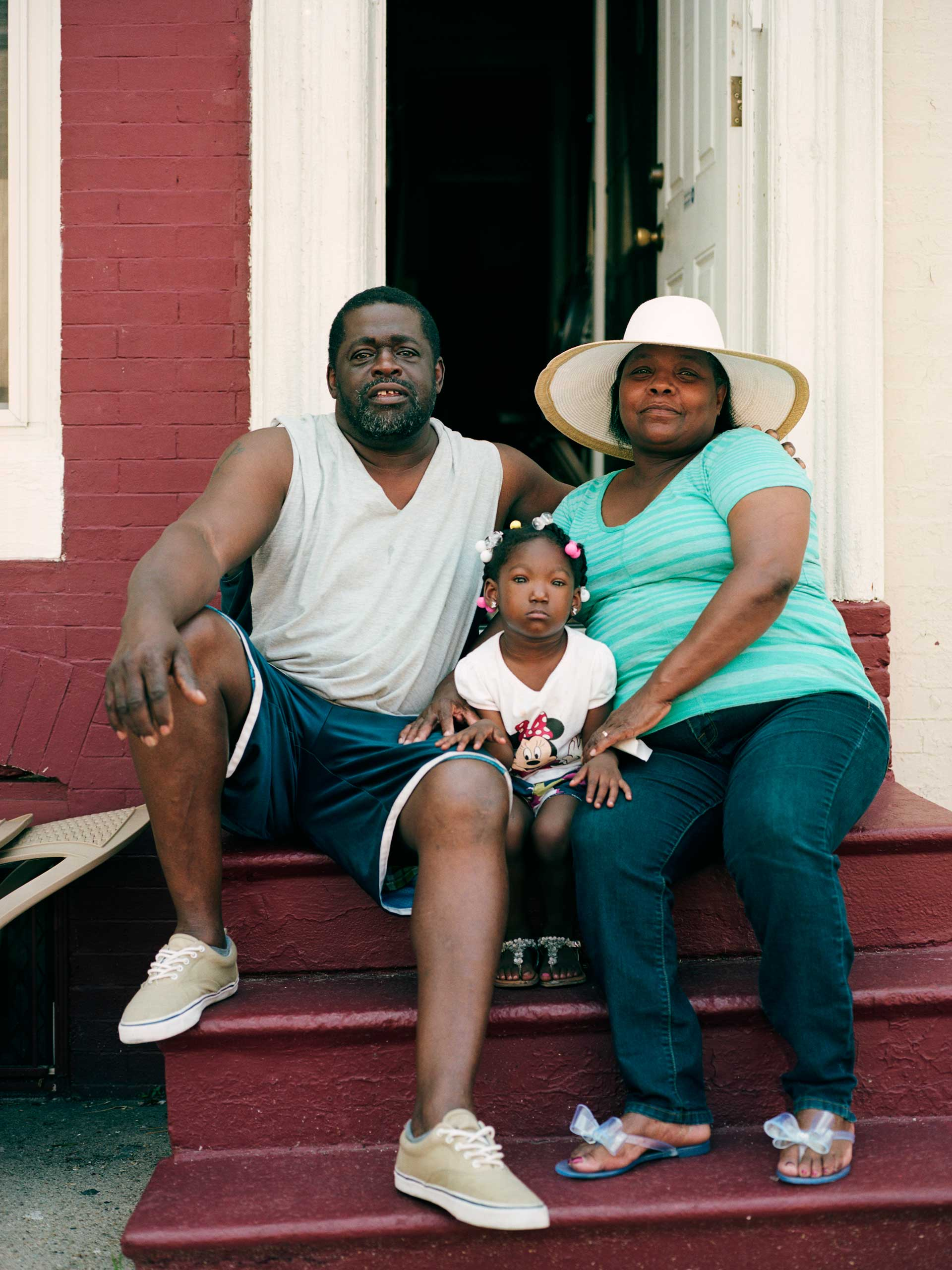 Kurt and Loretta Gardner sit on their stoop along with neighbor Jaelynn Harrison, 3. The Gardners have lived in this home on Laurens Street for over two decades and for years have sponsored an annual back to school block party over Labor Day weekend where they give away food, school clothes and supplies to families who need assistance.