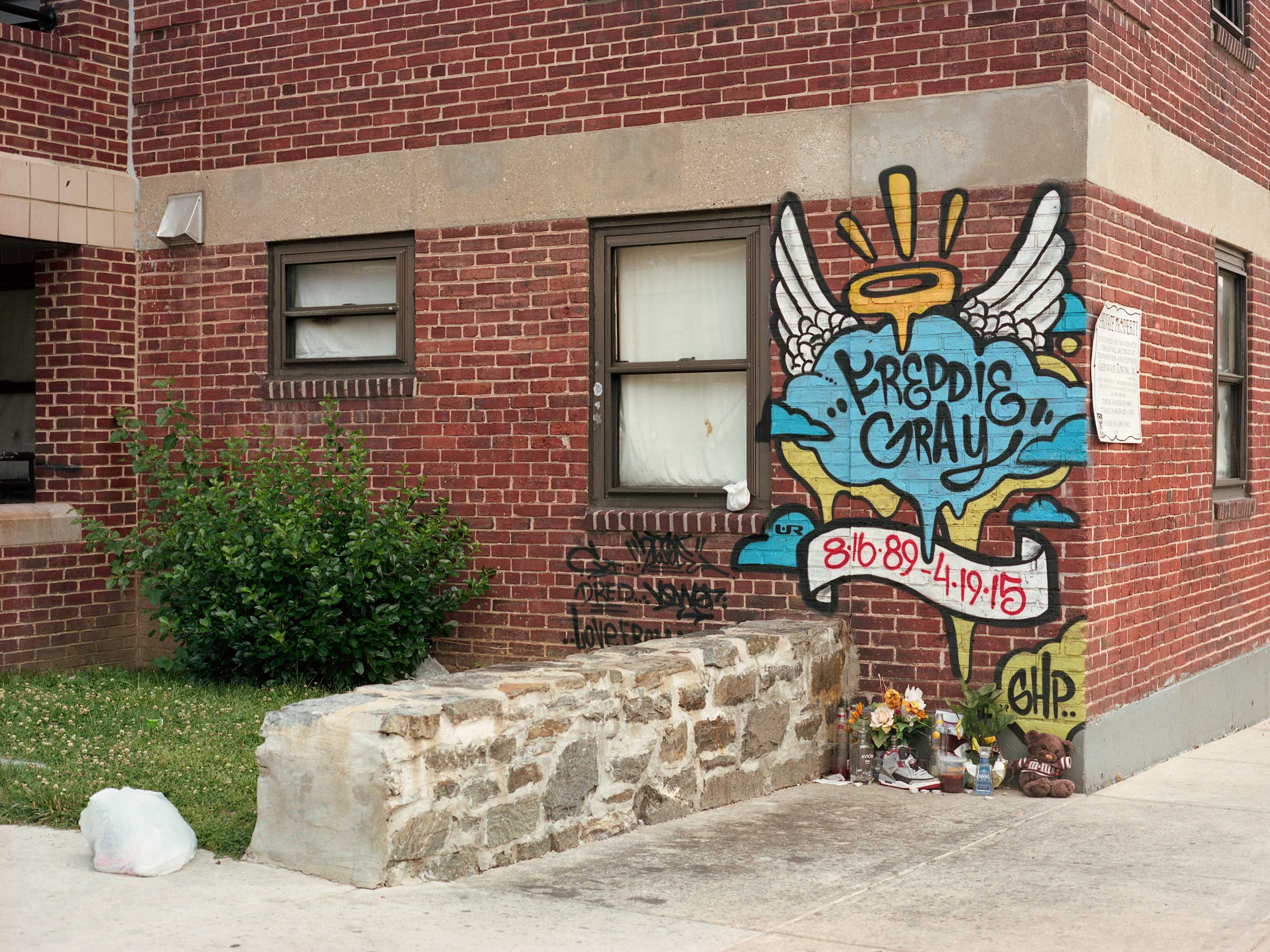 This is the exact location on Presbury Street near the Gilmor Homes housing project where Freddie Gray was thrown to the ground and arrested by Baltimore Police. The site is now a memorial with mementos frequent public gatherings.