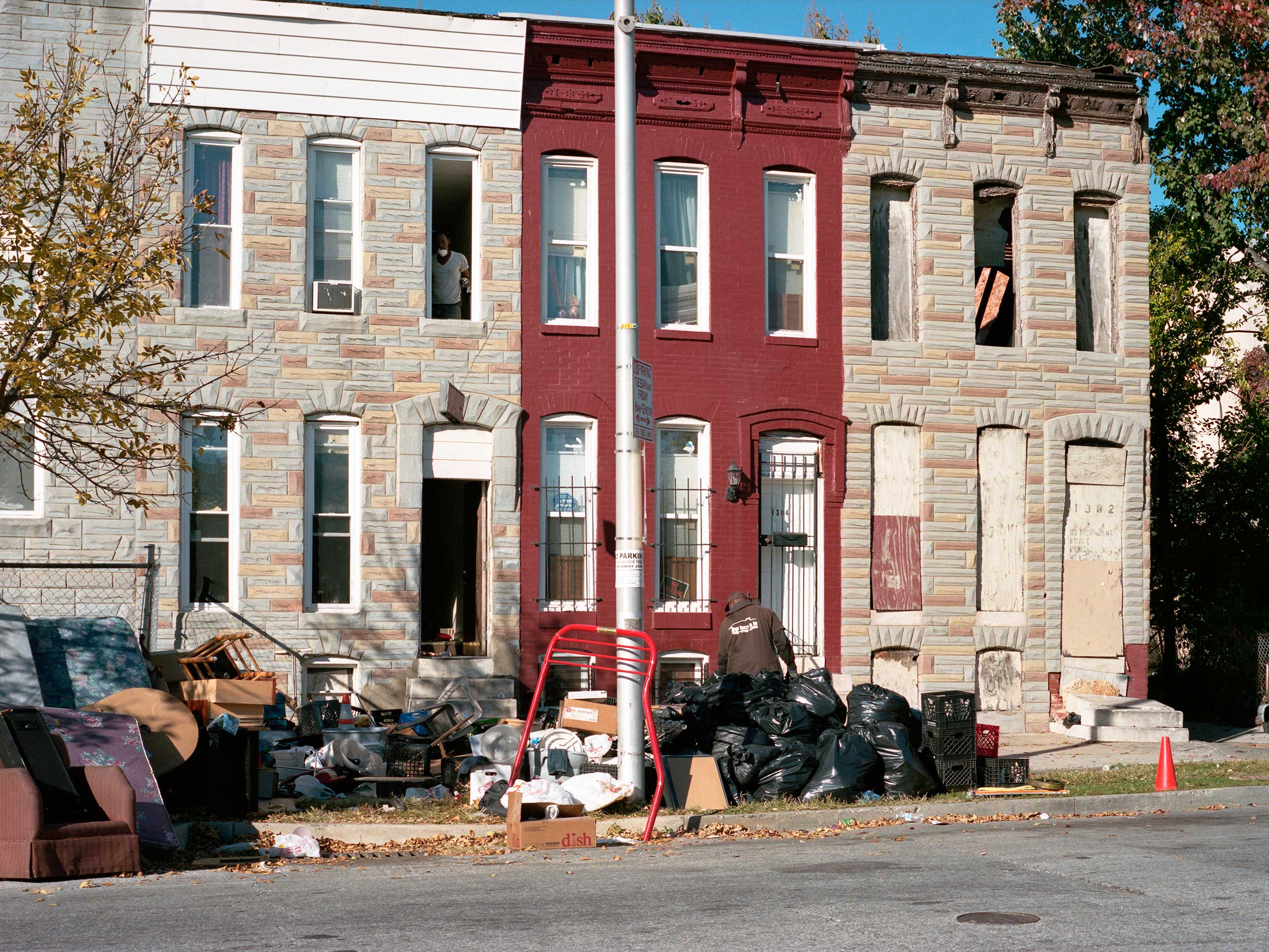 Local workers are hired to clear out a vacated row house on Riggs Avenue near North Carey Street after the tenants were evicted and abandoned many of their belongings in the process. The men sort the items into things that will be sold or trashed, yanking extension chords and other metal pieces from appliances in order to scrap them for extra cash.
