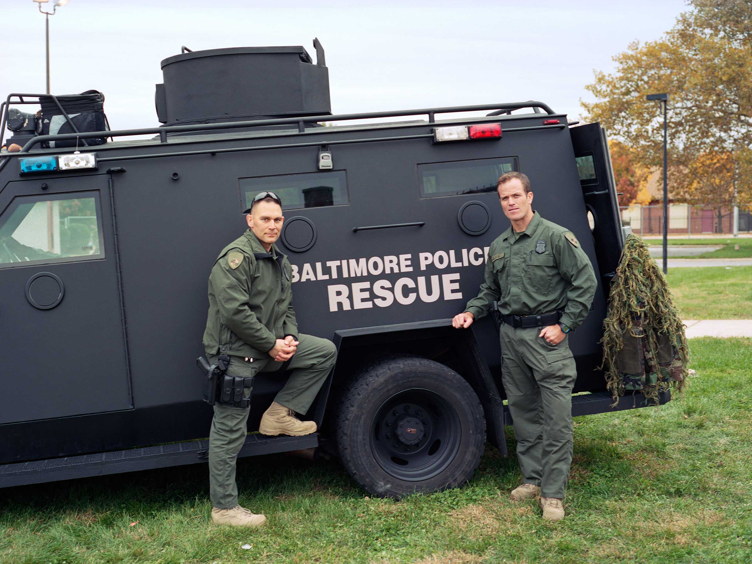 SWAT officers Dustin Schappell and Justin Merson stand beside their SWAT vehicle during a community event in Sandtown. The Baltimore Police SWAT team responds to 200 to 300 calls a year.