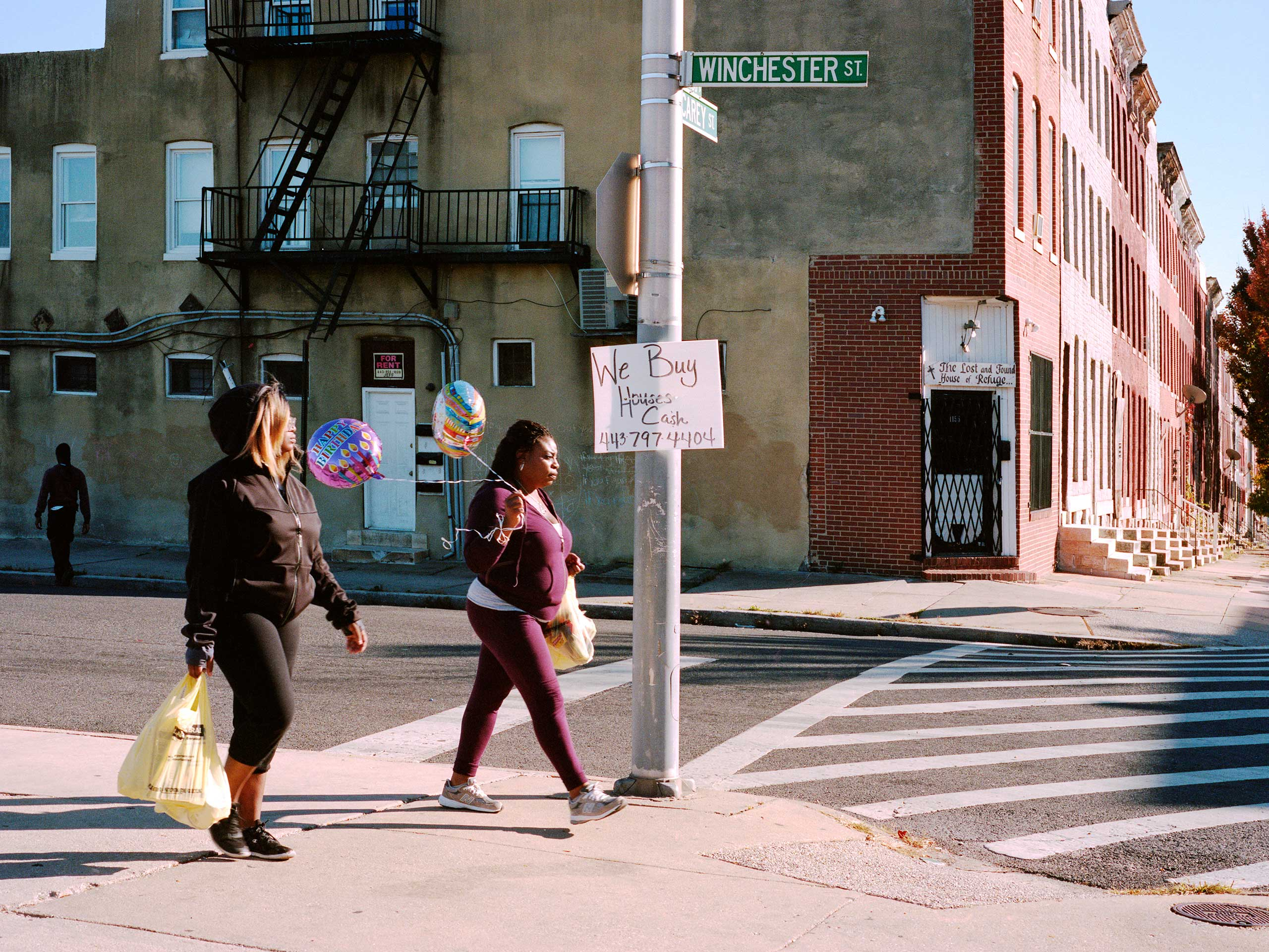 Two women walk past the corner of Winchester Street and North Carey Street carrying birthday balloons.