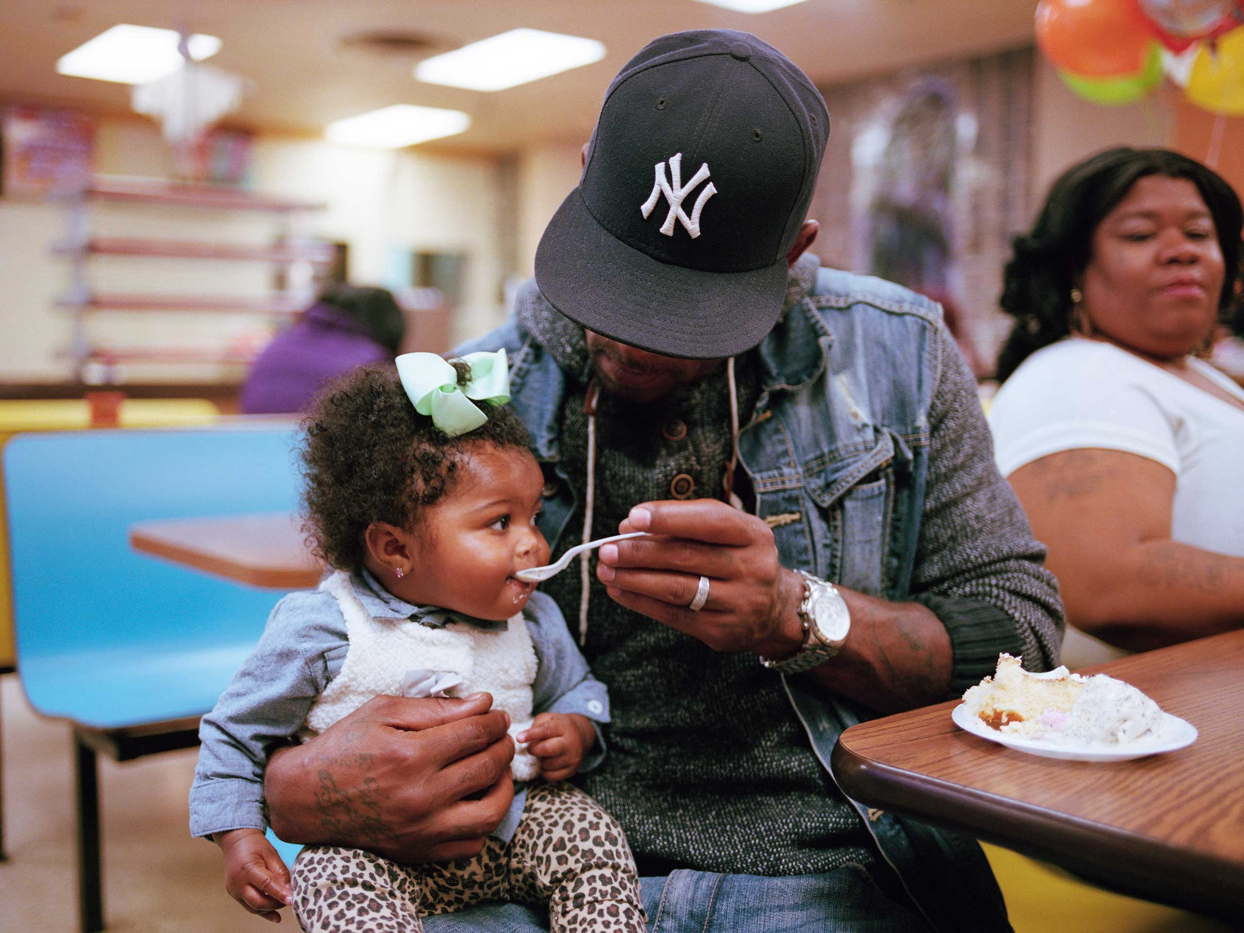 Duke Thomas feeds cake to his 8-month-old daughter Carter. They were at Shake and Bake, a local skating and bowling fun center, for a birthday party.