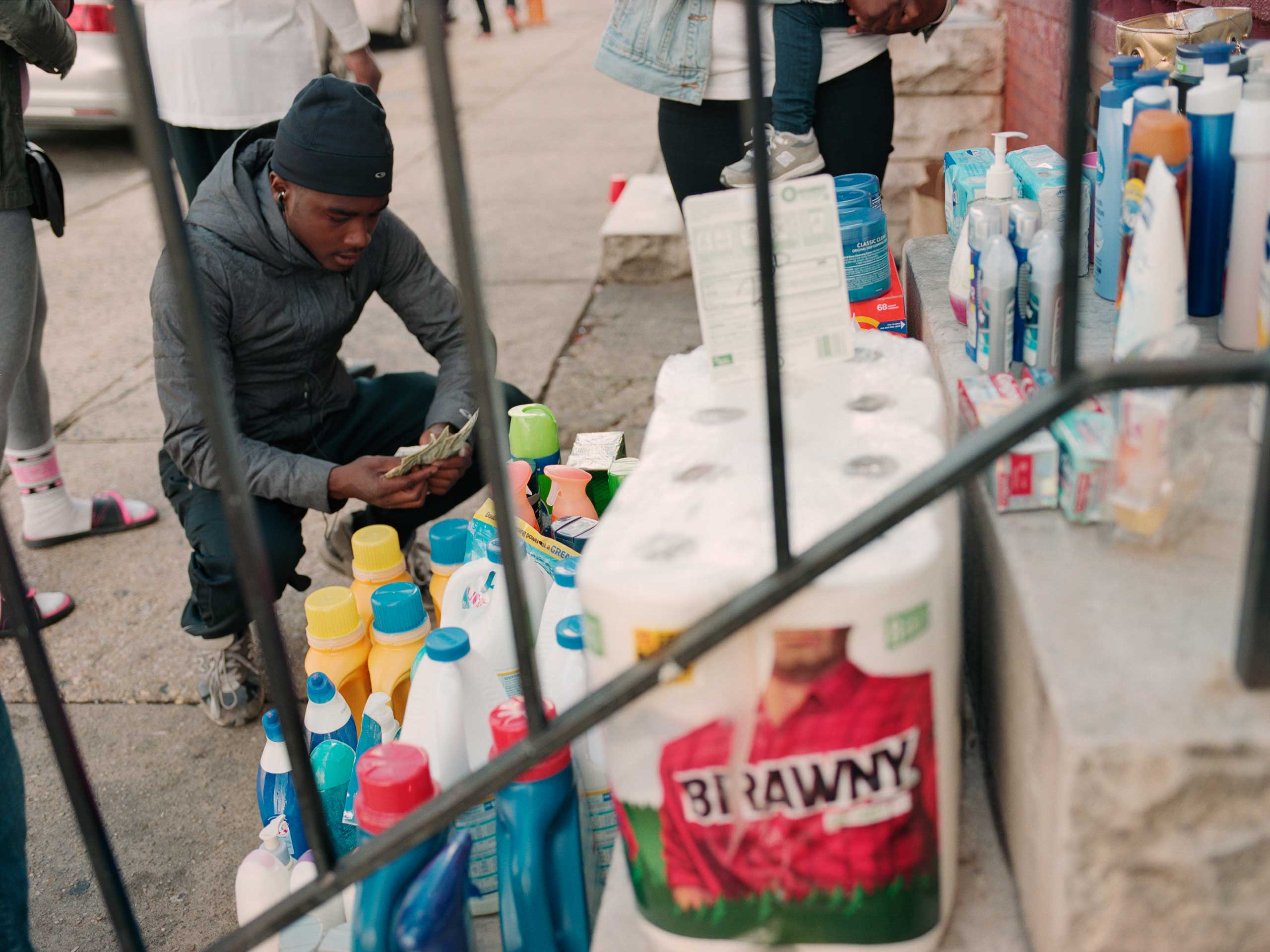 """A young man counts his money before making a purchase at the pop-up convenience store """"Smal-Mart,"""" which operates from a stoop on Calhoun Street near Westwood Avenue."""