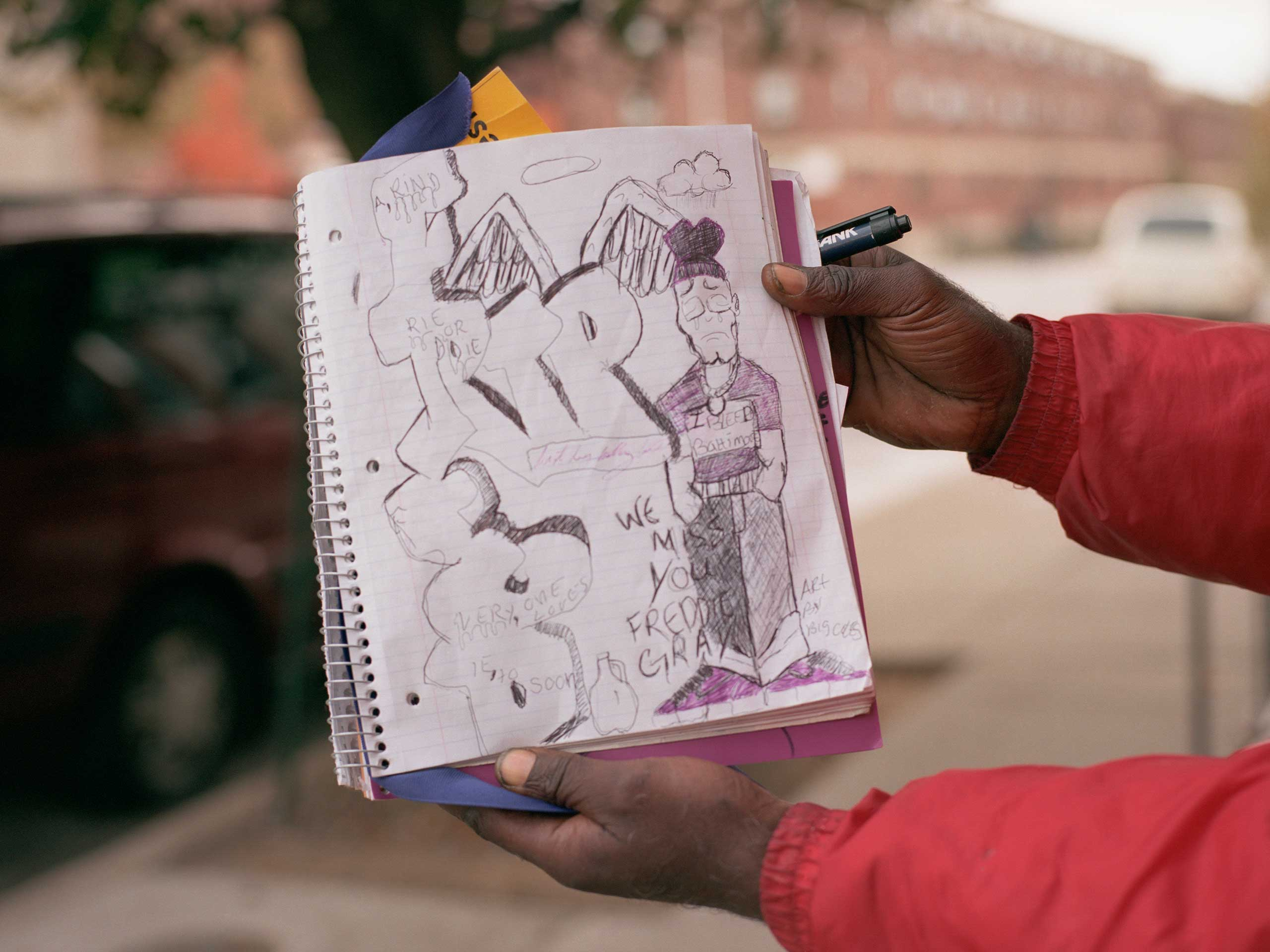 Anthony Coles holds up a drawing he made celebrating Freddie Gray.