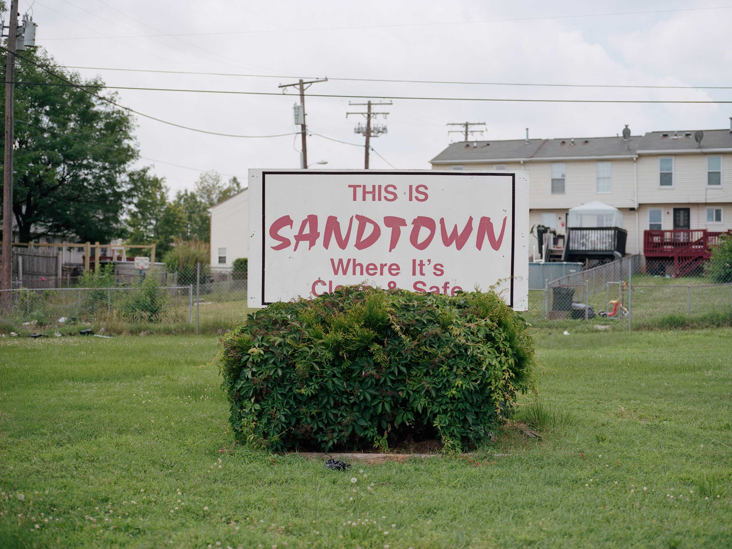 """A sign reads: """"This is Sandtown, where it is clean and safe."""""""