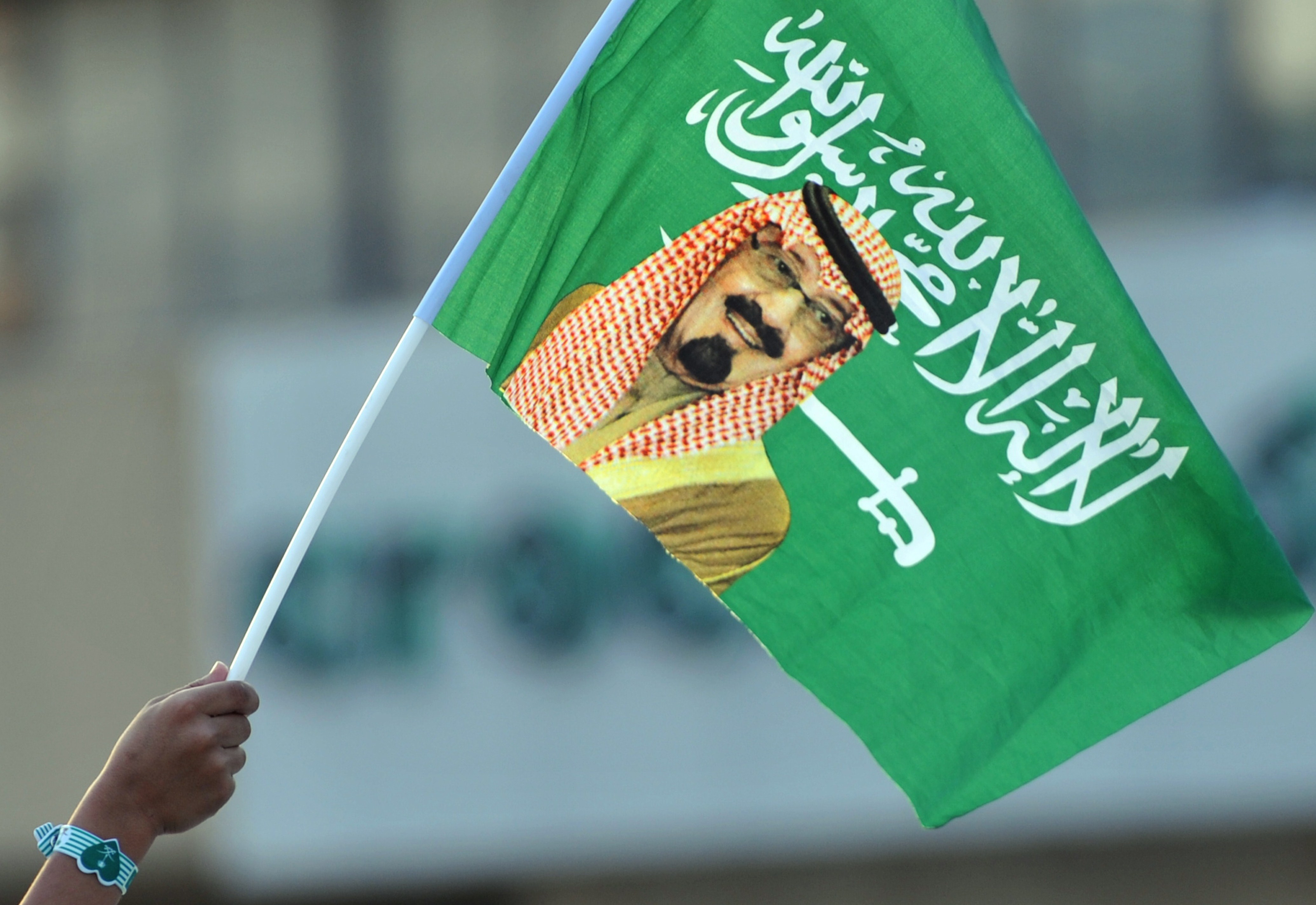 A Saudi child holds up a national flag with picture of King Abdullah bin Abdulaziz, on Sept. 23, 2013.