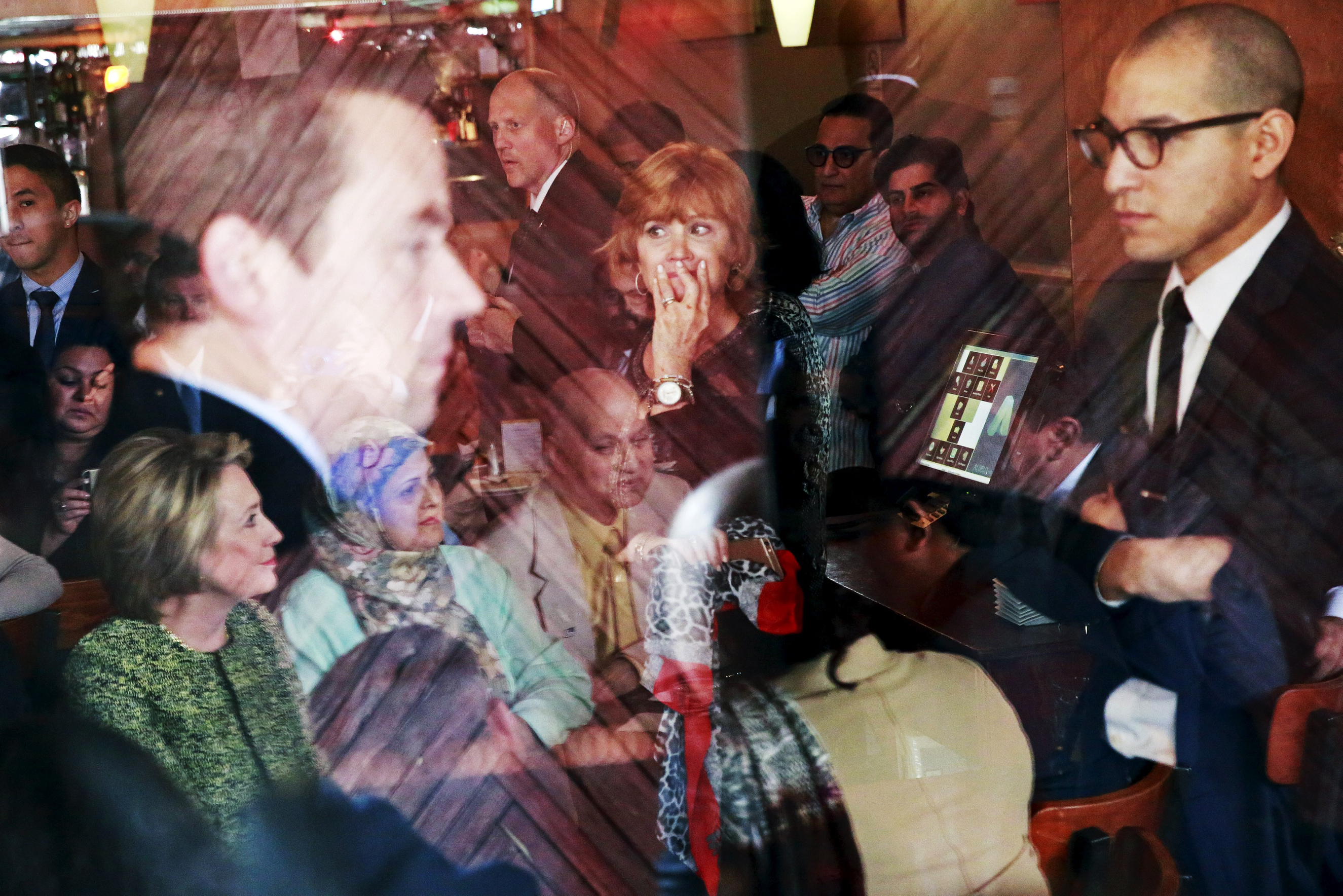 Patrons, security personnel, and members of the community gather to listen to Democratic presidential candidate Hillary Clinton during a visit to the Jackson Diner in New York's Queens borough on April 11, 2016.
