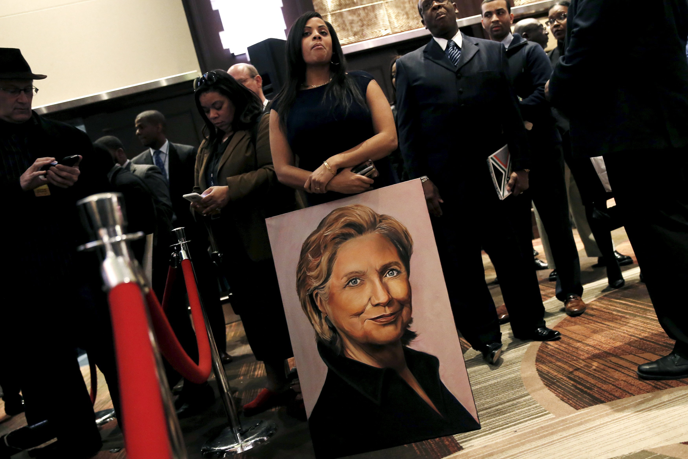 A supporter of Hillary Clinton stands with a painting at the National Action Network's 25th Annual Convention in New York on April 13, 2016.
