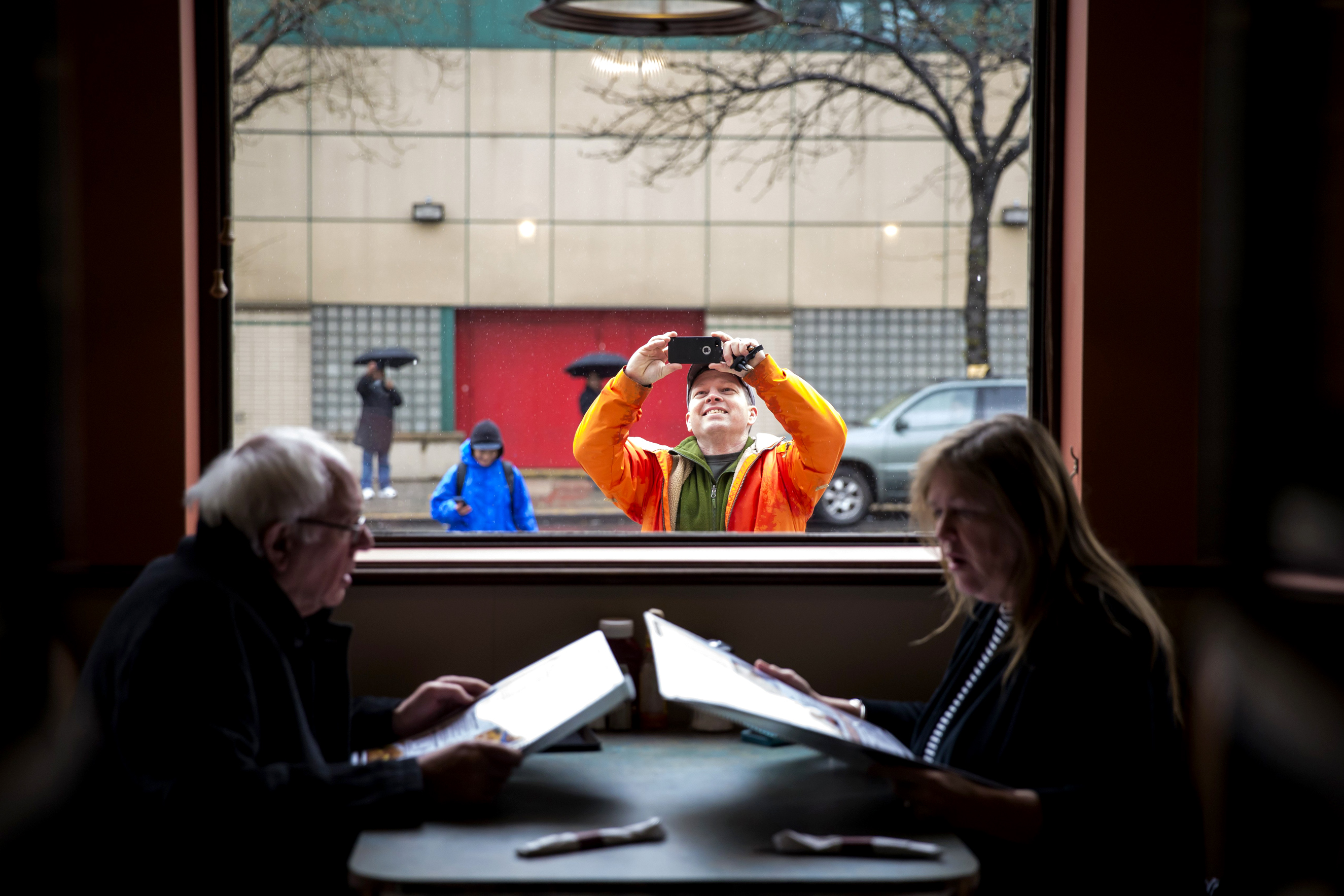 A man takes a picture of  Sen. Bernie Sanders (D-VT) and his wife Jane at the Van Dam diner on April 9, 2016 in New York's Queens borough.