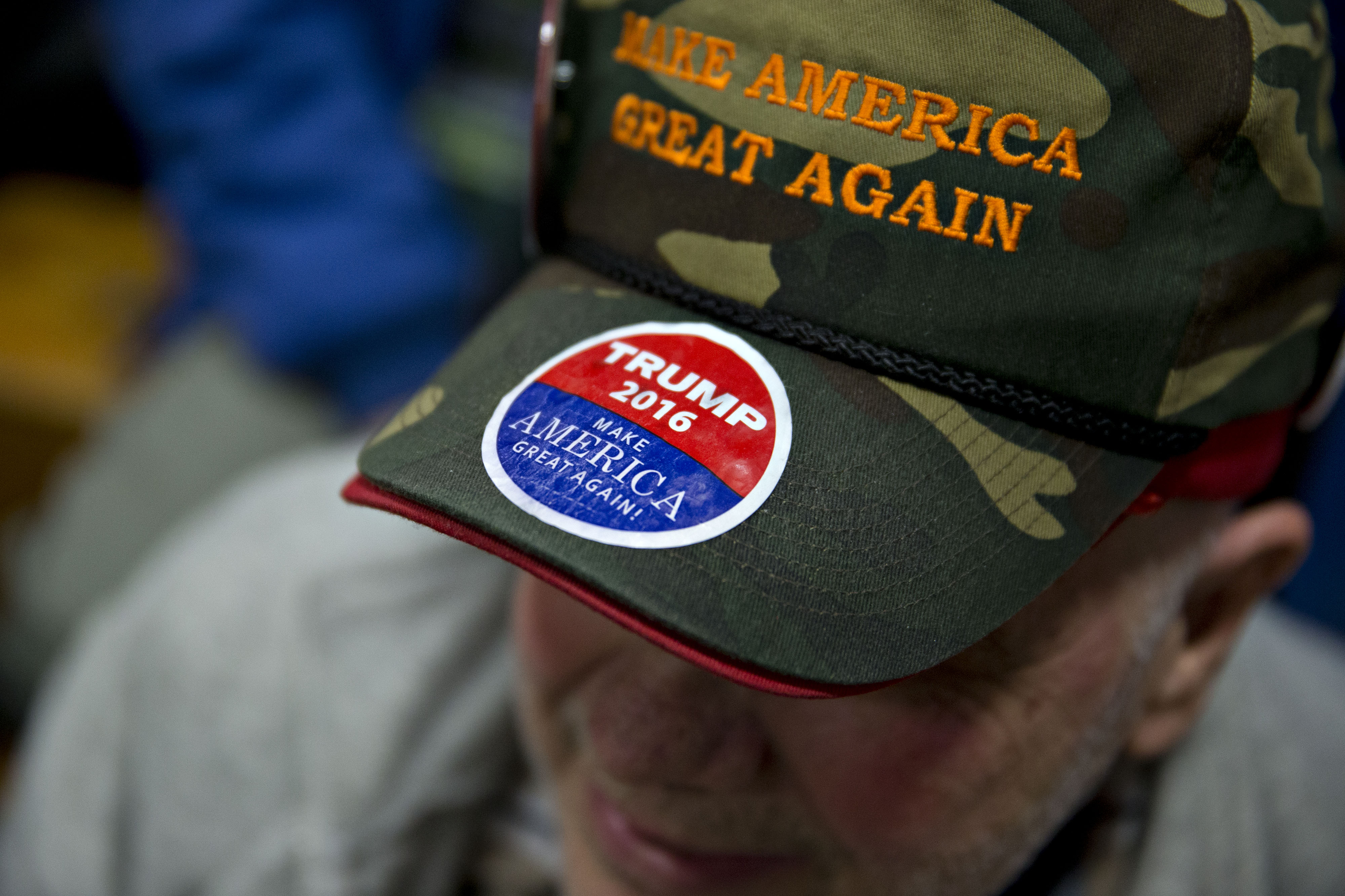 Attendee Rich Travers wears a  Make America Great Again  hat before Donald Trump, president and chief executive of Trump Organization Inc. and 2016 Republican presidential candidate, not pictured, speaks during a campaign rally at Pennichuck Middle School in Nashua, New Hampshire, U.S., on Monday, Dec. 28, 2015.