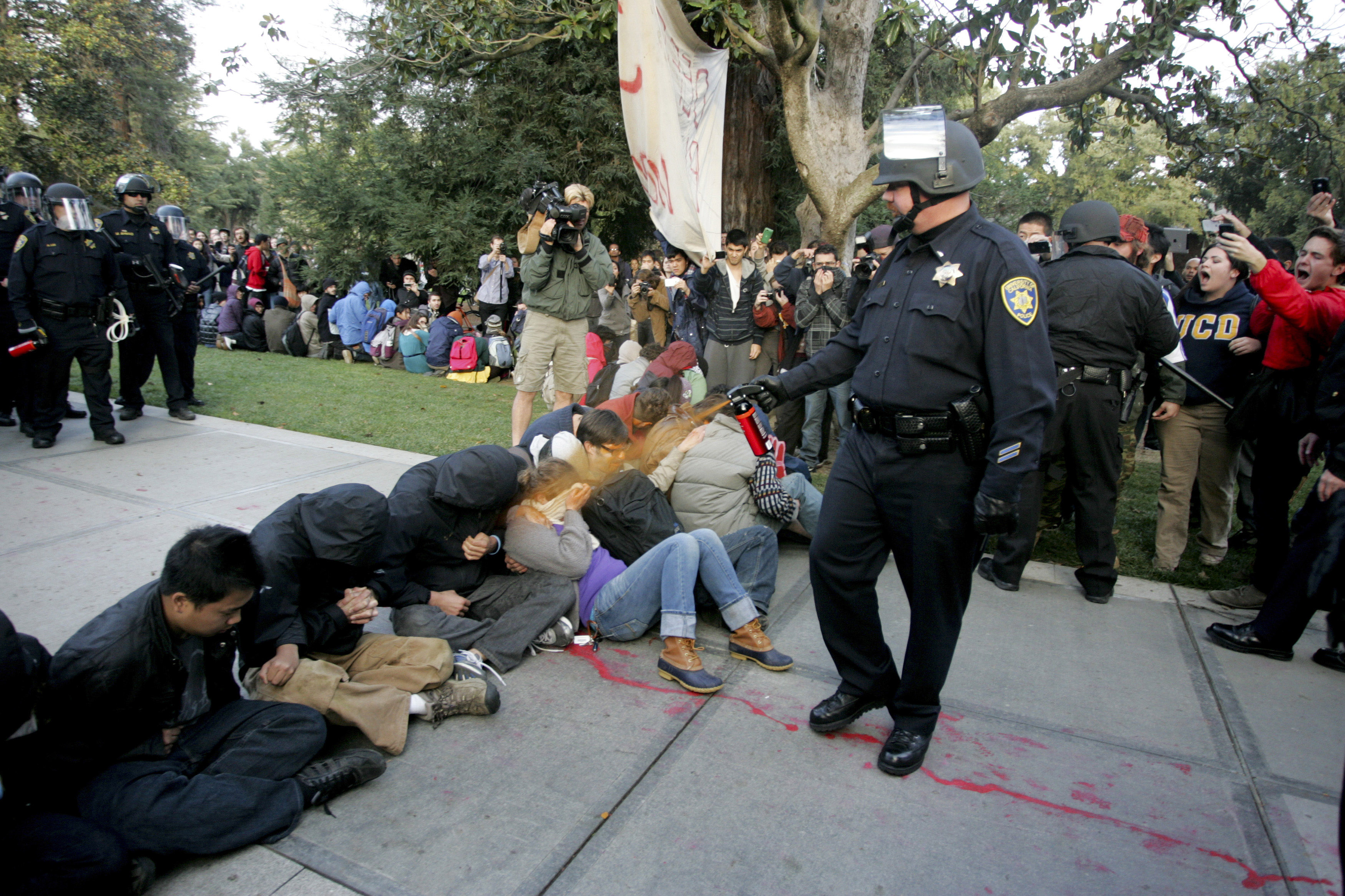 A University of California Davis police officer pepper-sprays students during their sit-in at an  Occupy UCD  demonstration in Davis, Calif. on Nov. 18, 2011.
