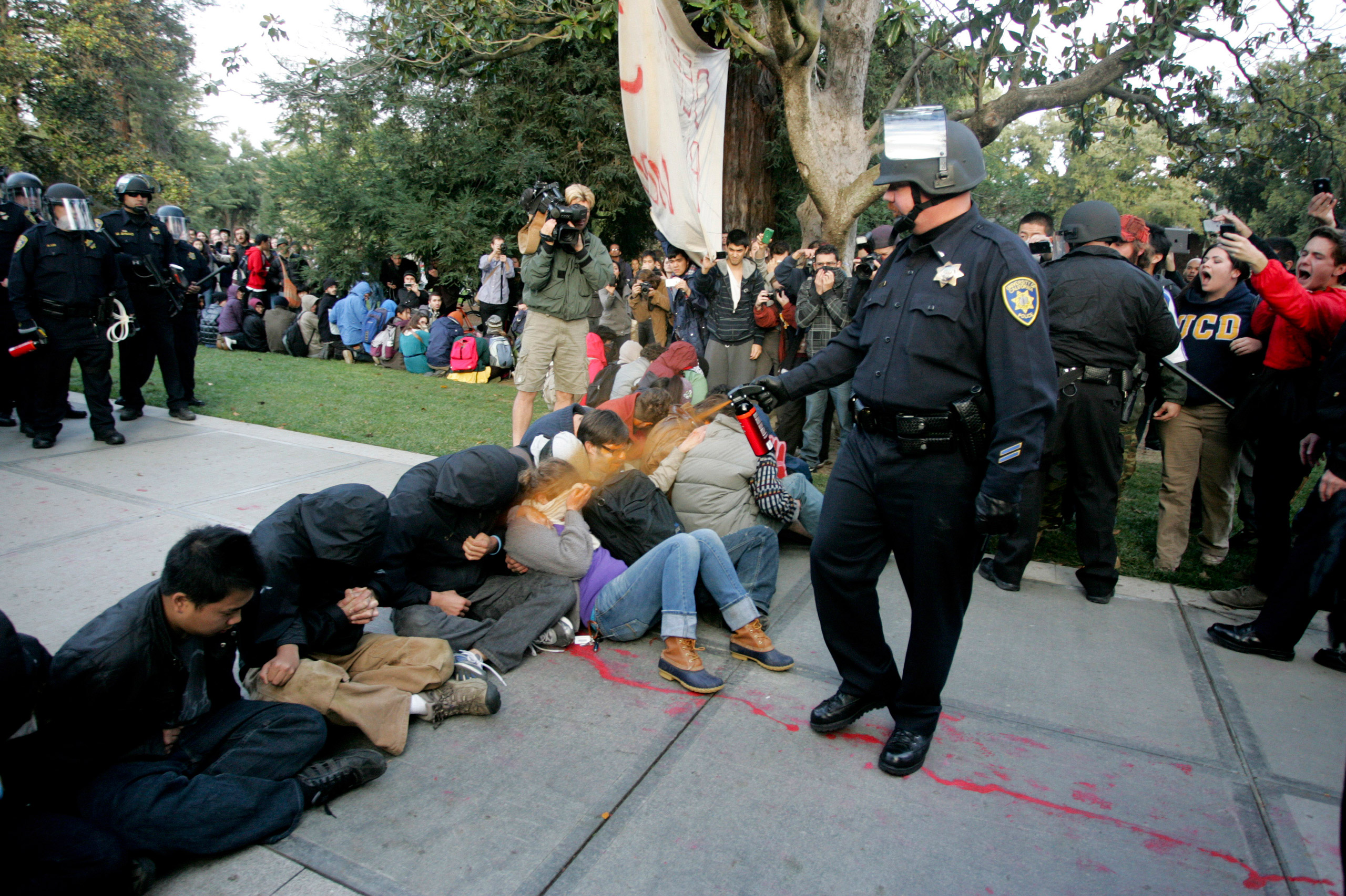 A University of California Davis police officer pepper-sprays students during their sit-in at an  Occupy UCD  demonstration in Davis, California November 18, 2011.  UC Davis Chancellor Linda Katehi apologized to jeering students on November 21 for police use of pepper spray against campus protesters in a standoff captured by video and widely replayed on television and the Internet. Faculty and student critics of Friday's confrontation, some of whom demanded the chancellor's resignation, said it had damaged the school's image and the climate for free expression at the university. Photo taken November 18, 2011.  REUTERS/Brian Nguyen  (UNITED STATES - Tags: CIVIL UNREST EDUCATION CRIME LAW TPX IMAGES OF THE DAY) - RTR2UCTQ