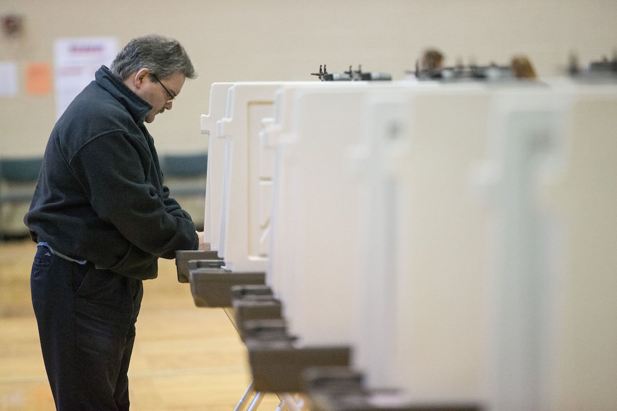 A voter marks his ballot for the Michigan presidential primary at a polling station in Warren, Michigan, March 8, 2016.