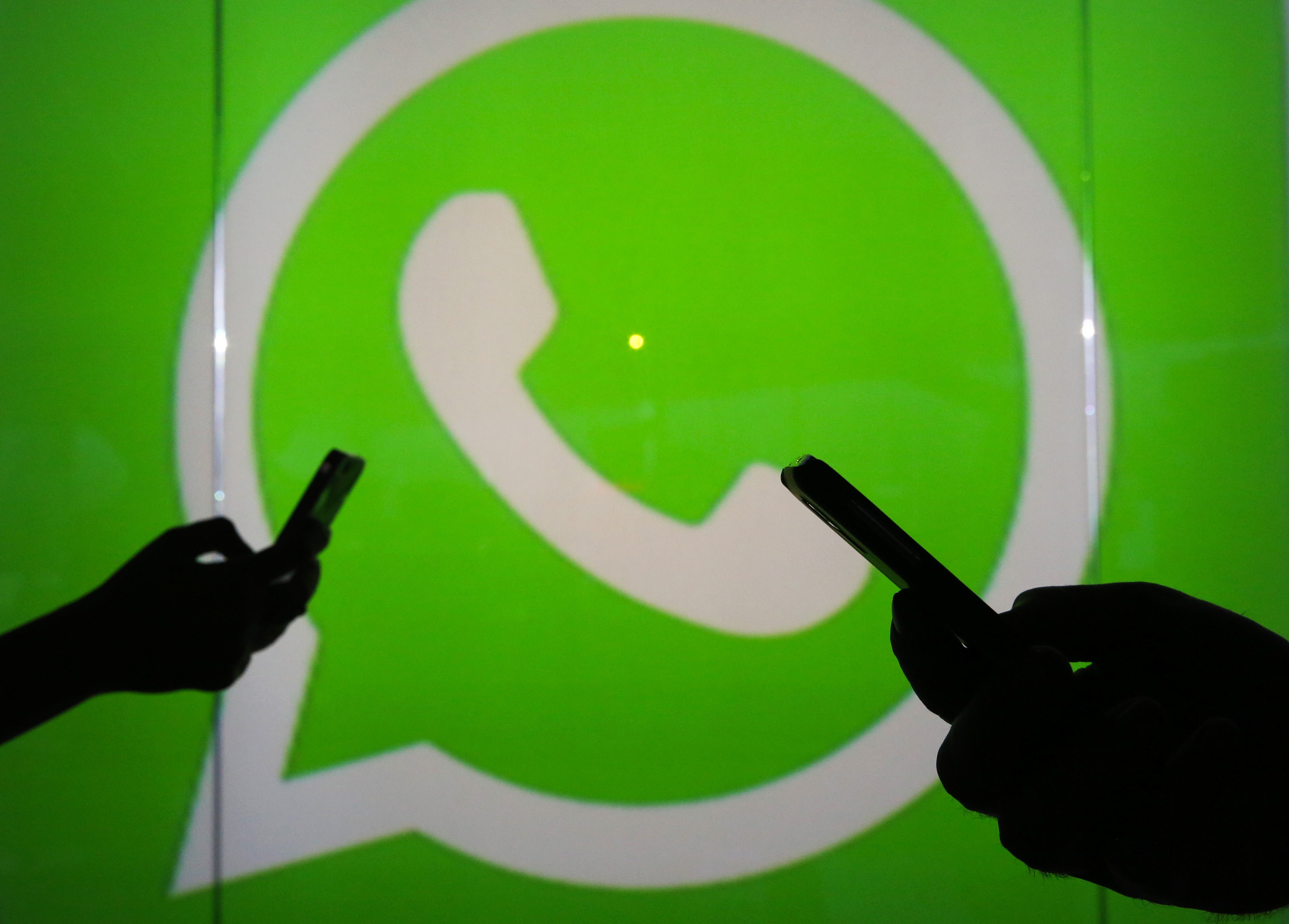 People are seen as silhouettes as they check mobile devices whilst standing against an illuminated wall bearing WhatsApp Inc's logo.
