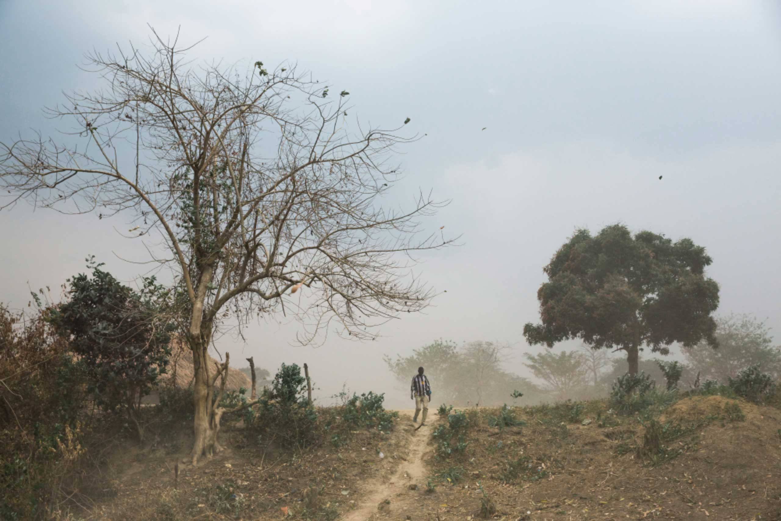 A man walks on a path outside the village of Zawara, situated on the Oubangui River about 24 miles east of Bangui, Central African Republic. Though relatively close to the capital, Zawara is nonetheless isolated due to a lack of roads and transport options.