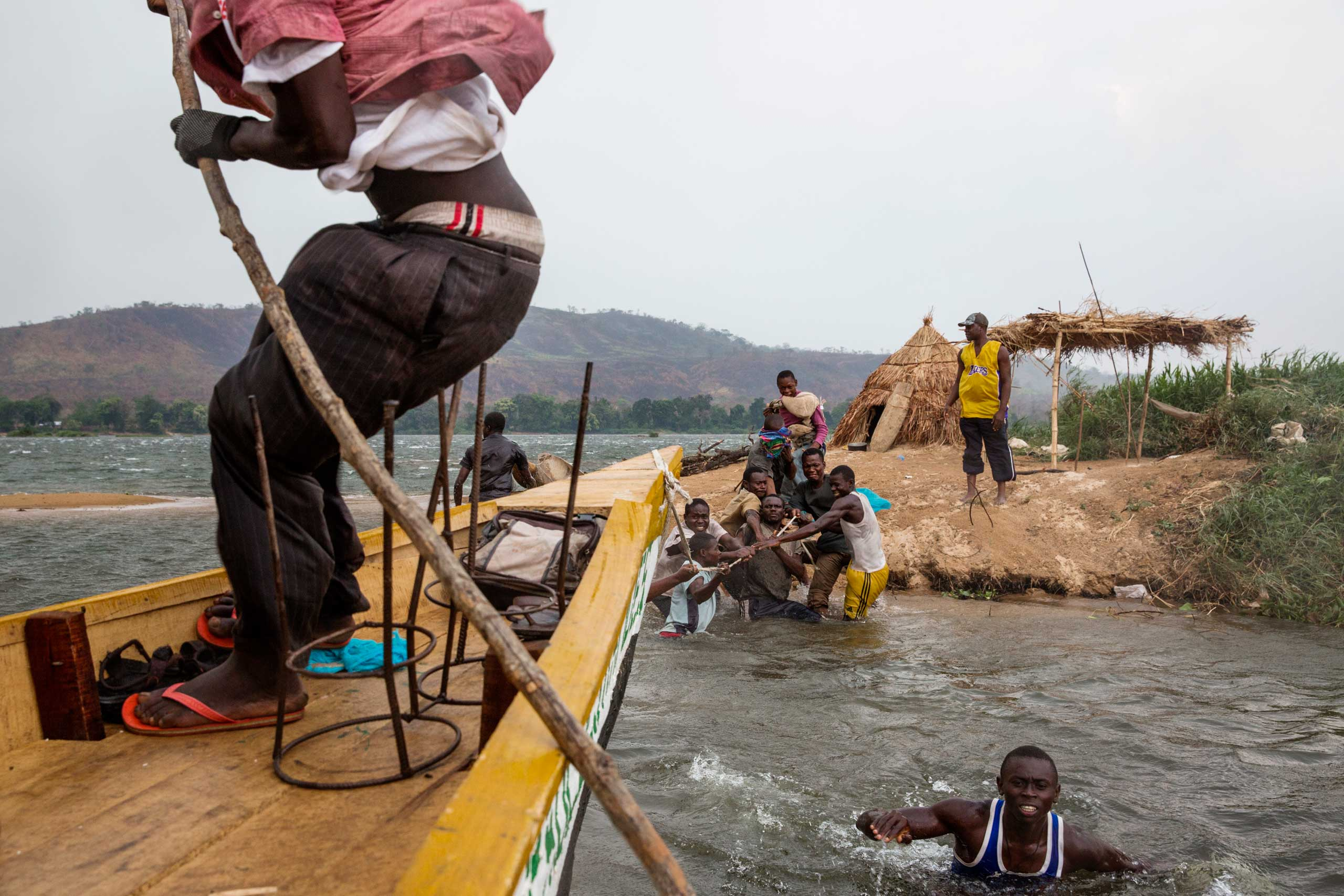 Because of a wind storm on the Oubangui river, a boat carrying goods and cows had to stop.